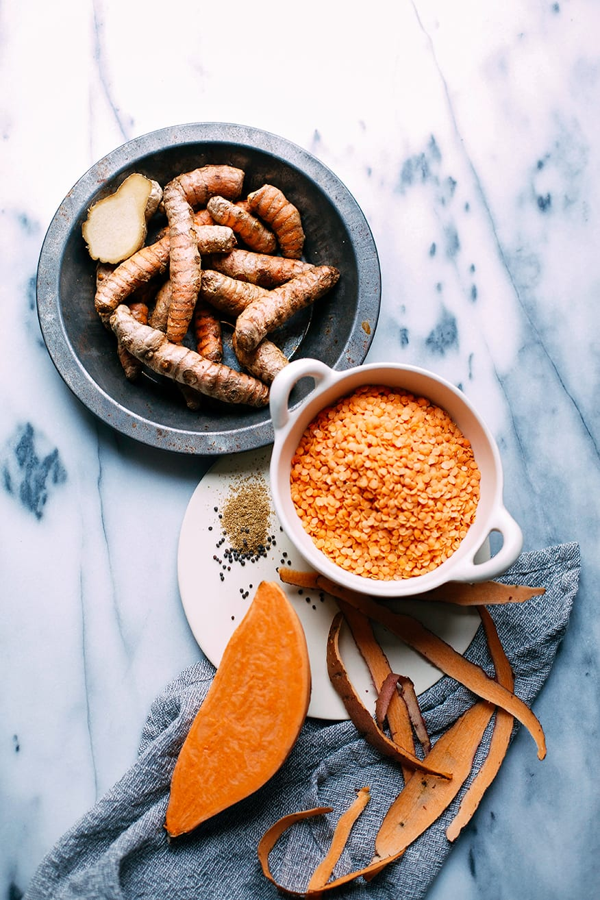 An overhead shot of ingredients for a sweet potato dal recipe: fresh turmeric roots, red lentils, sweet potatoes, and spices.