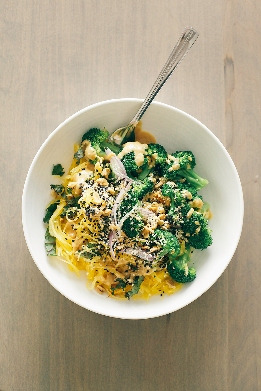 An overhead shot of a spaghetti squash noodle bowl with bright green broccoli florets and a tan peanut sauce drizzled over the top. It is in a white bowl on a beige wood background.