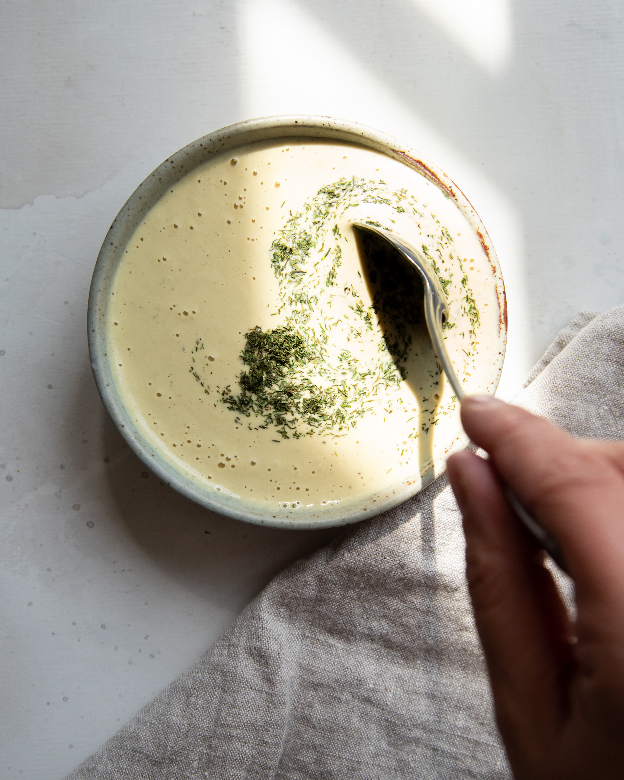 Image shows a hand stirring dried dill into a bowl of creamy dressing.