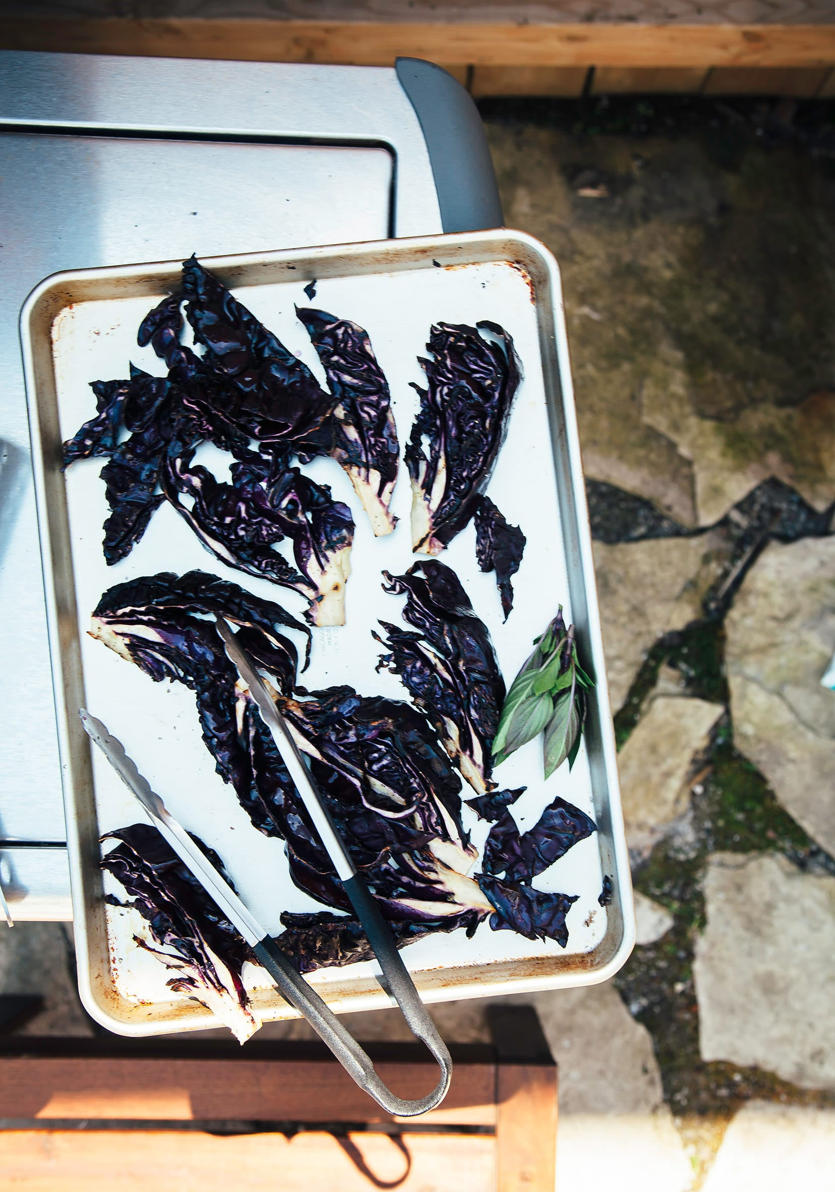 An overhead shot of grilled purple cabbage wedges on a baking sheet, outdoors.