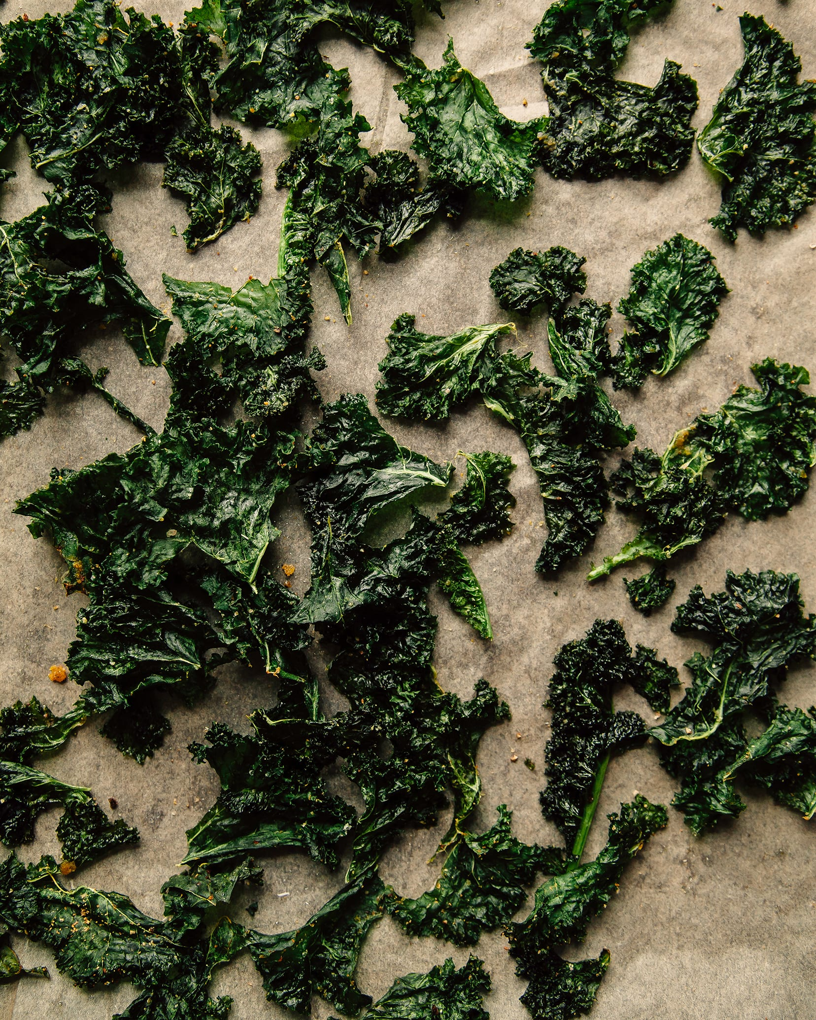 An overhead shot of crispy roasted kale on a parchment paper-lined baking sheet.