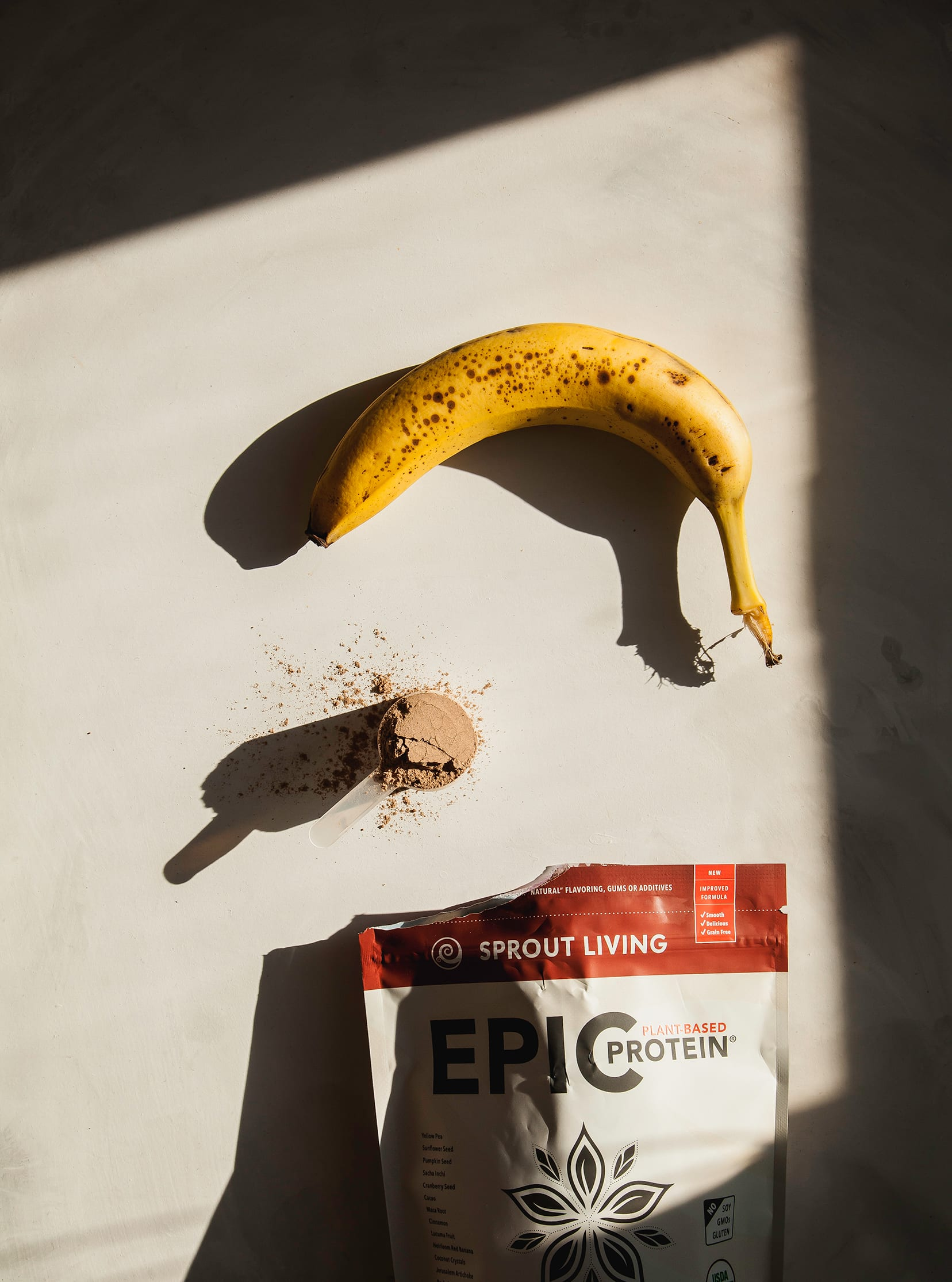 An overhead shot of a ripe banana and a scoop of protein powder in direct sunlight with strong shadows.