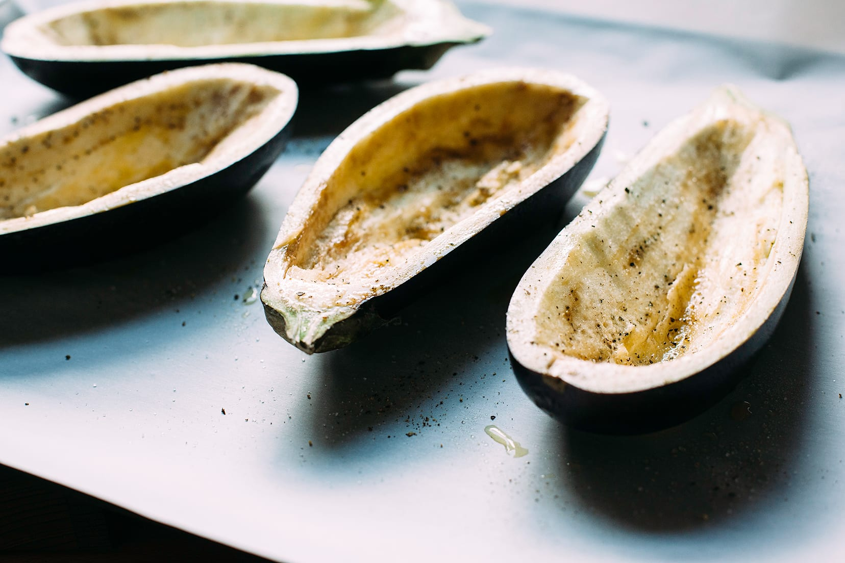"""Image shows hollowed out eggplant """"shells"""" on a baking sheet."""