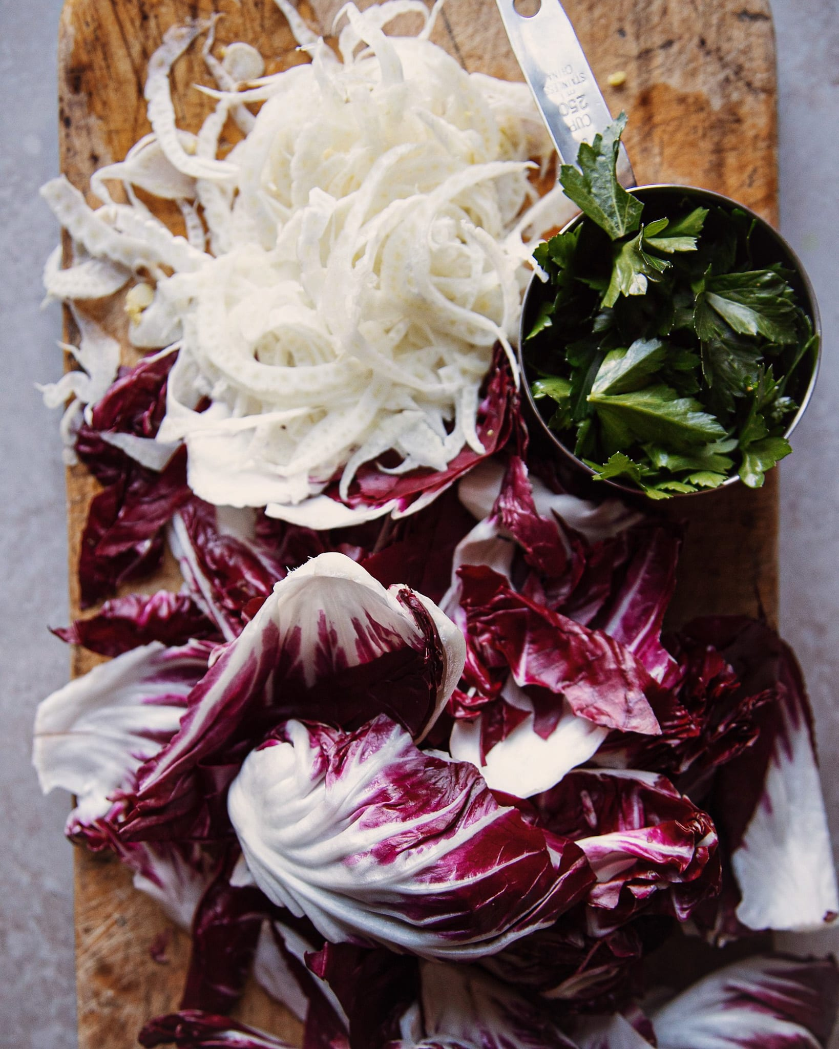 Torn radicchio, shaved fennel and a cup of parsley leaves on a wood chopping board.