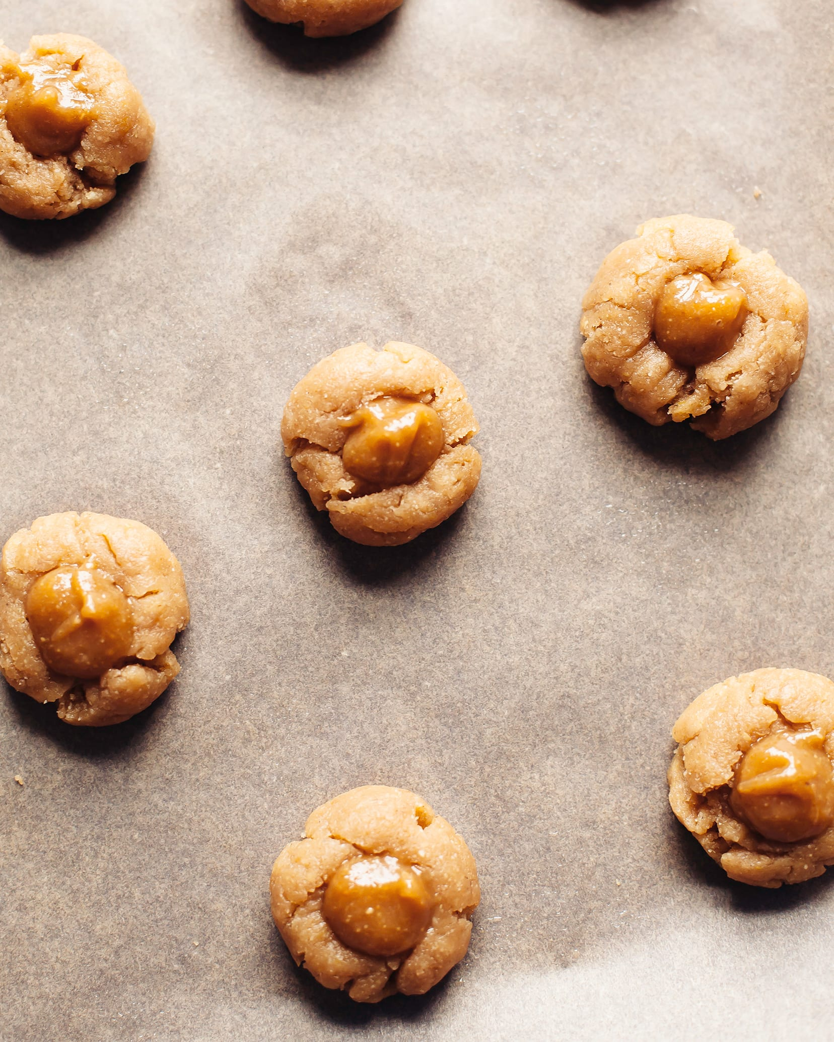 Overhead shot of thumbprint cookies before they go in the oven, on parchment paper.