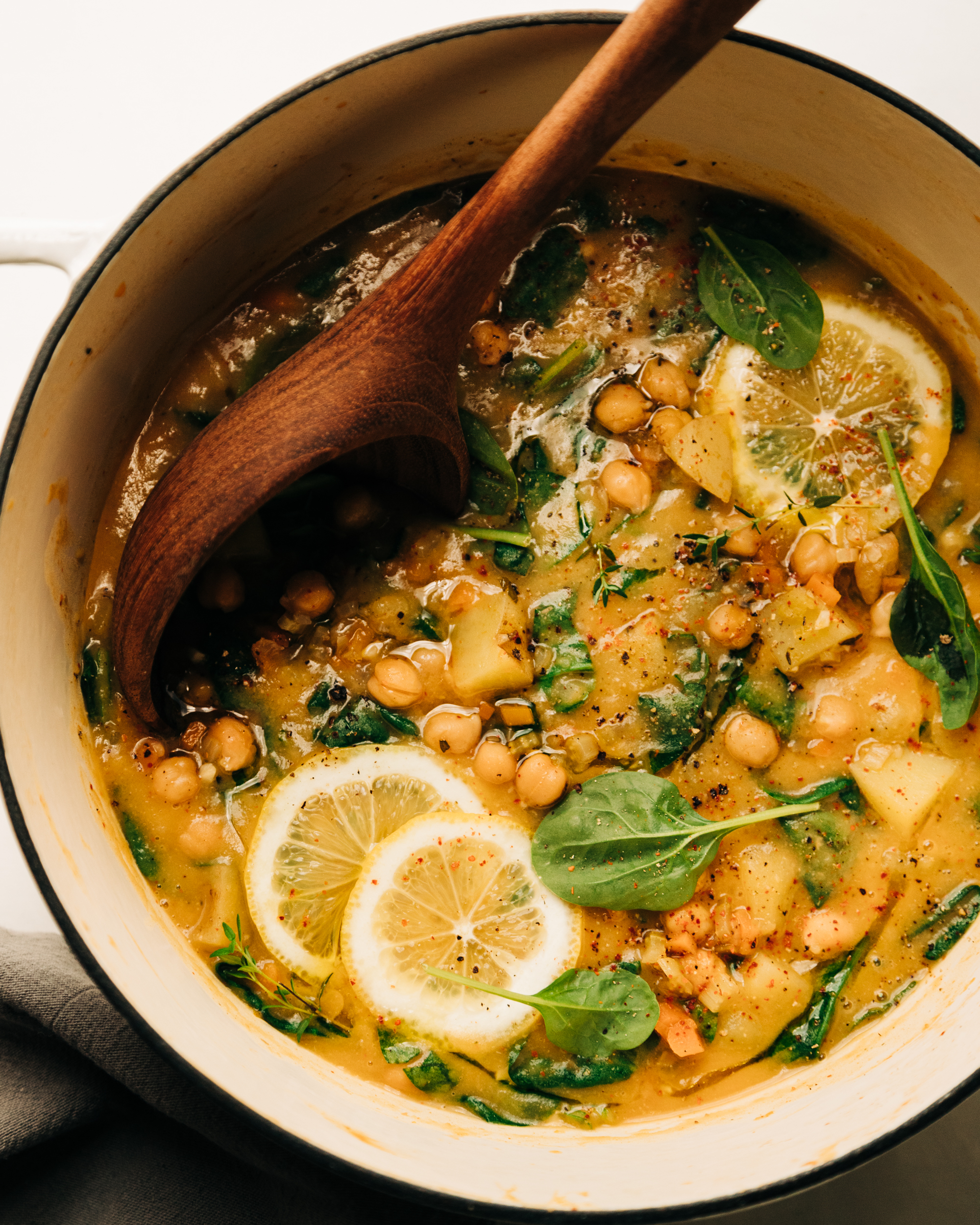 An overhead shot of a creamy and thick lemony chickpea soup with spinach and potatoes. A wooden ladle is sticking out of the pot.