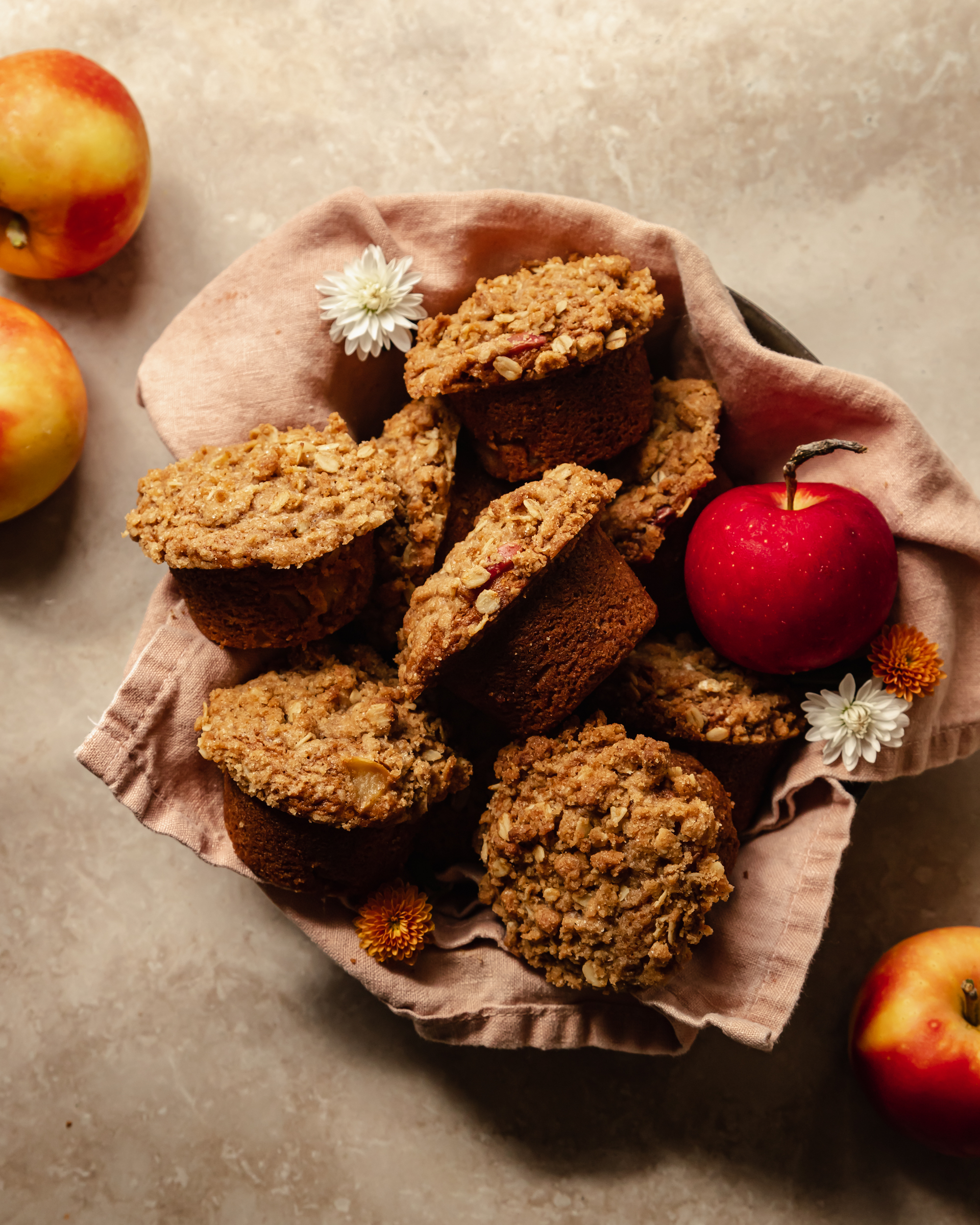 An overhead shot of crumble topped muffins set inside of a pink linen in a bowl. An apple is shown to the side.