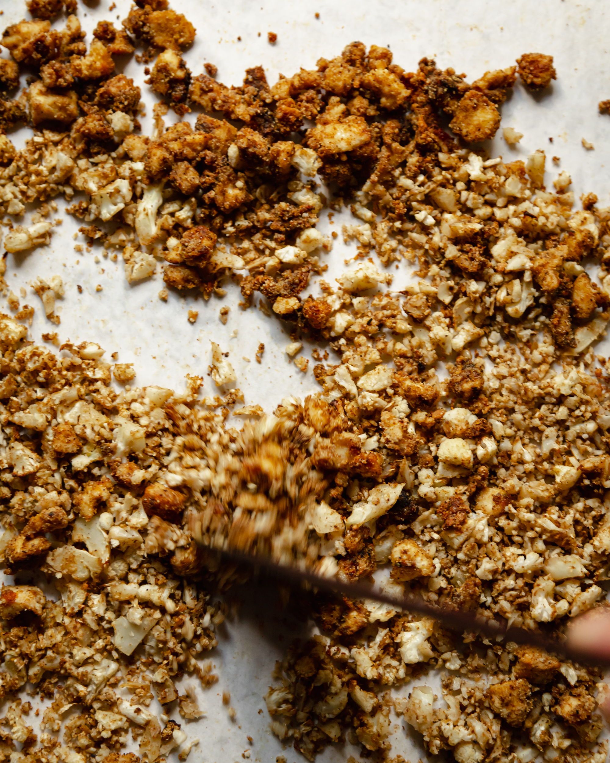 An overhead shot of roasted cauliflower rice and crispy coated bits of tofu being stirred up on a parchment-lined baking sheet.