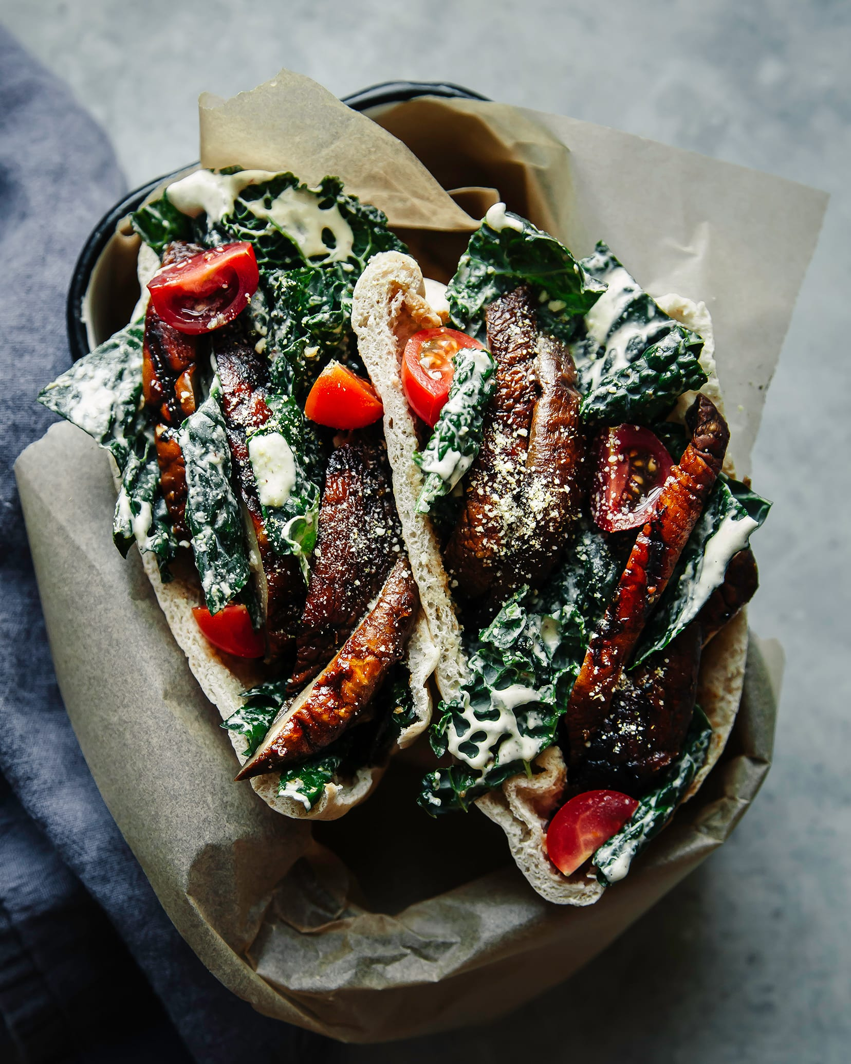 An up close, overhead shot of two pitas stuffed with creamy-dressed kale, sliced grilled mushrooms and quartered cherry tomatoes. The pitas are inside a small rectangular dish on top of a blue-ish grey background.