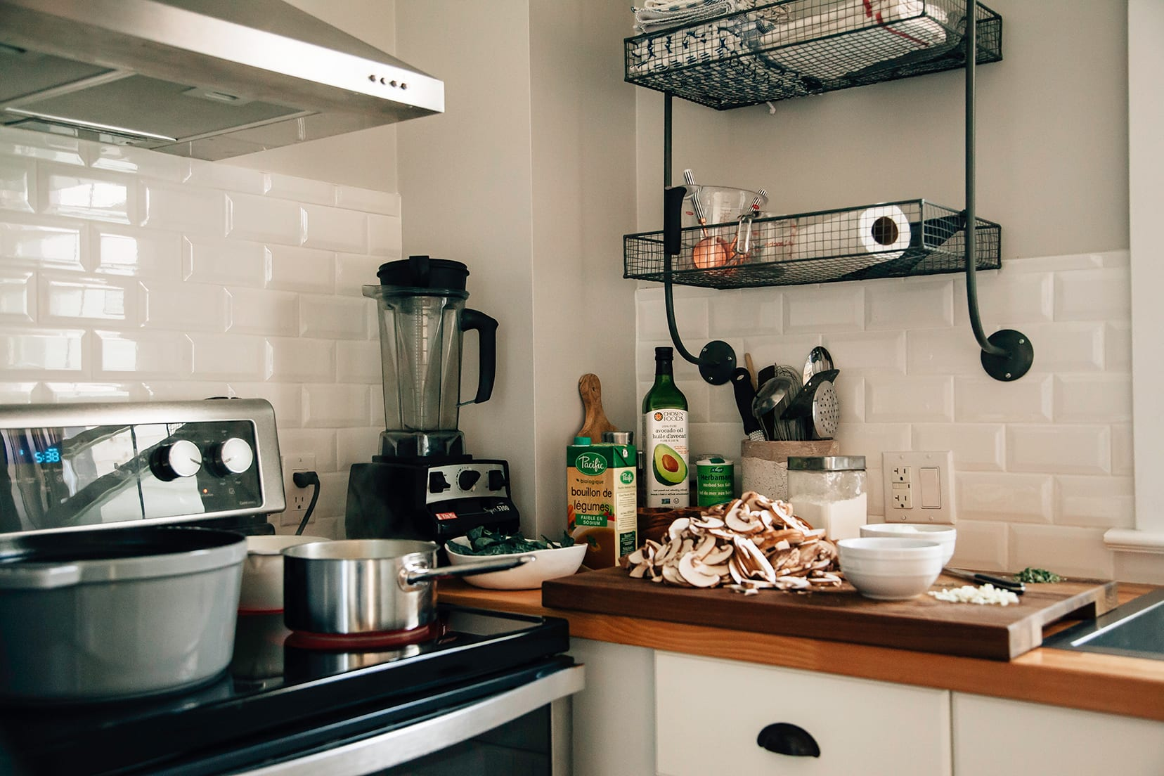 Image shows a kitchen scene with pots on the stove and a cutting board with sliced mushrooms on top.