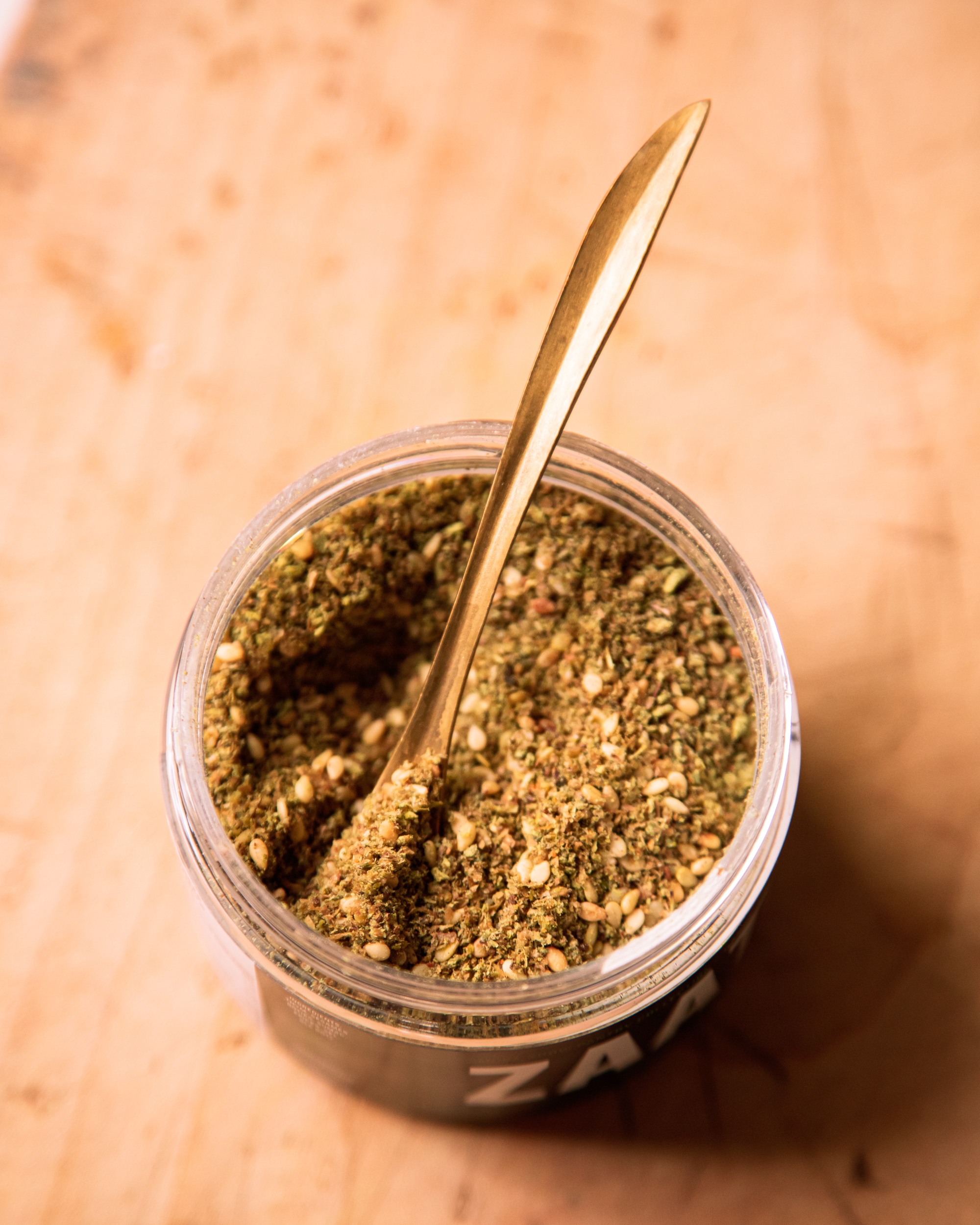 An up close shot of a jar of za'atar spice with a gold spoon sticking out.