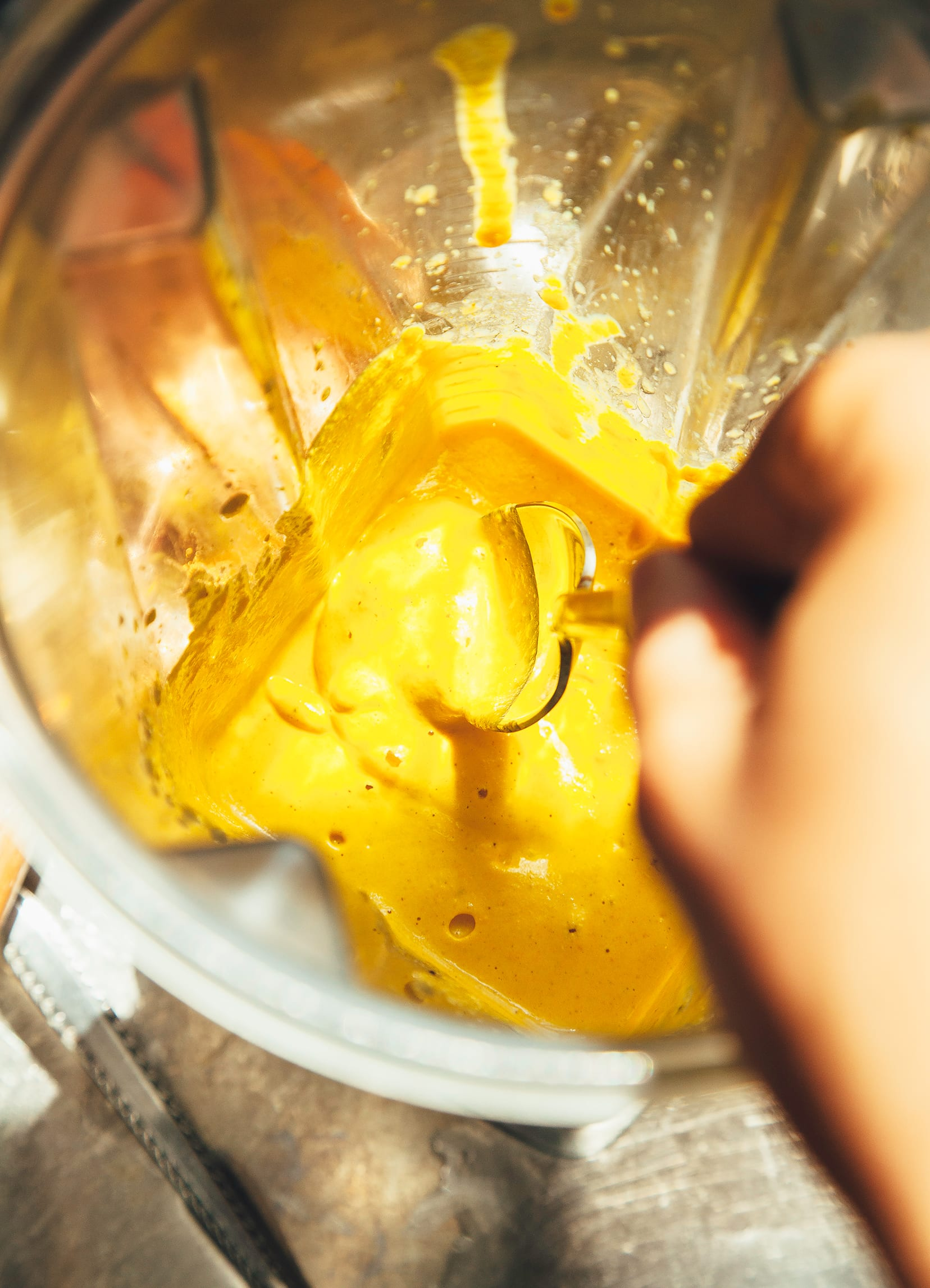 Image shows hand dipping a spoon into a blender of creamy, yellow sauce.