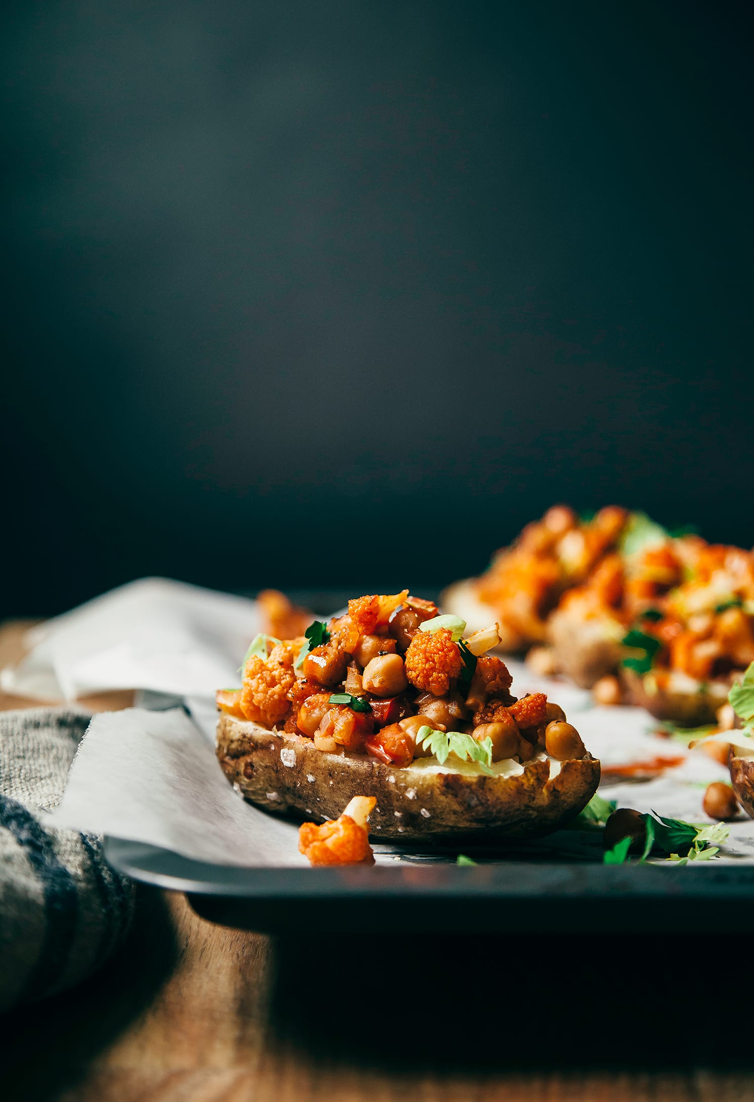 A head-on shot of a baked potato half filled with cauliflower, chickpeas, and Buffalo-style hot sauce.