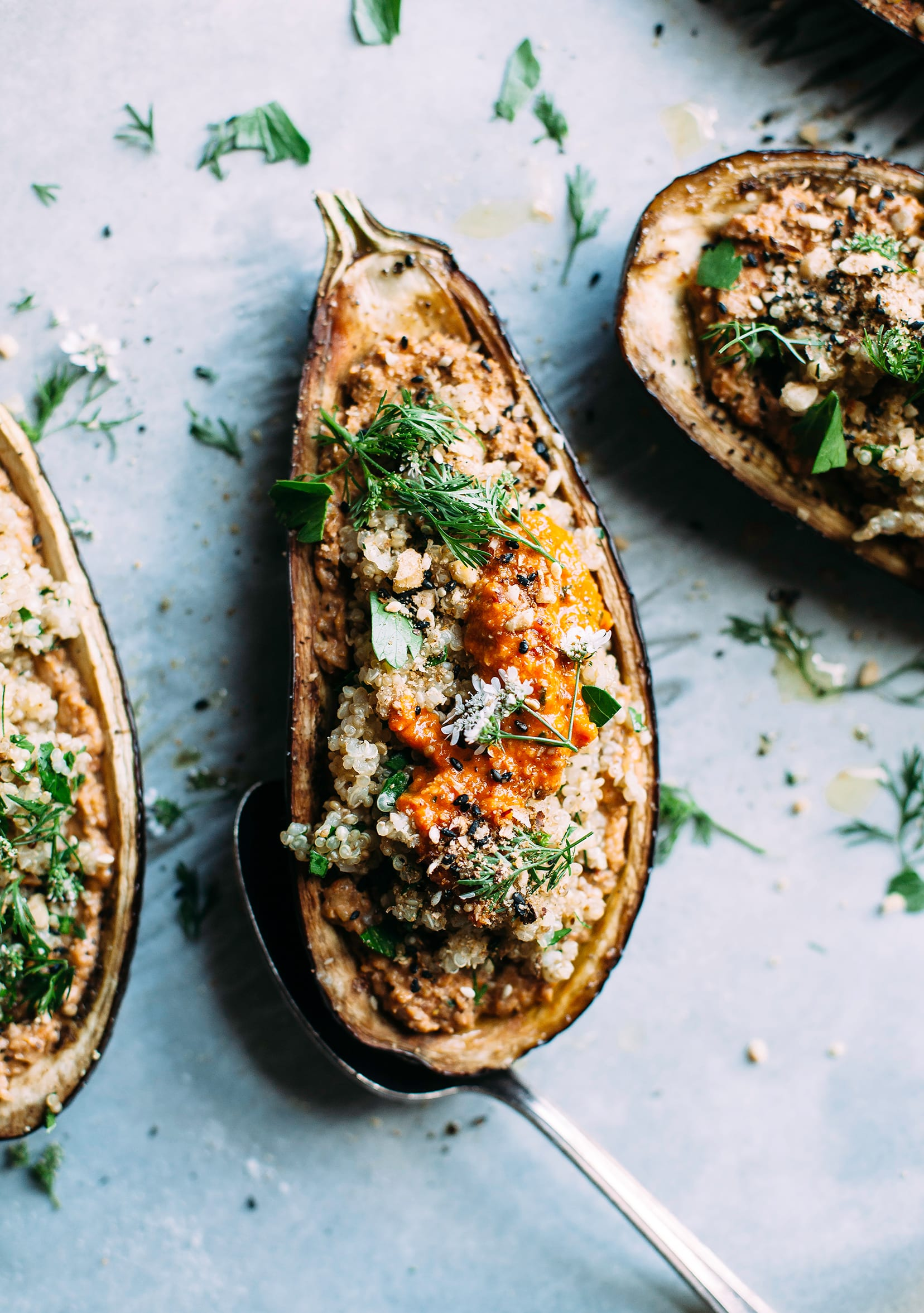 """An overhead shot of a stuffed eggplant """"boat"""" with grains inside and a dab of a deep red/orange sauce."""