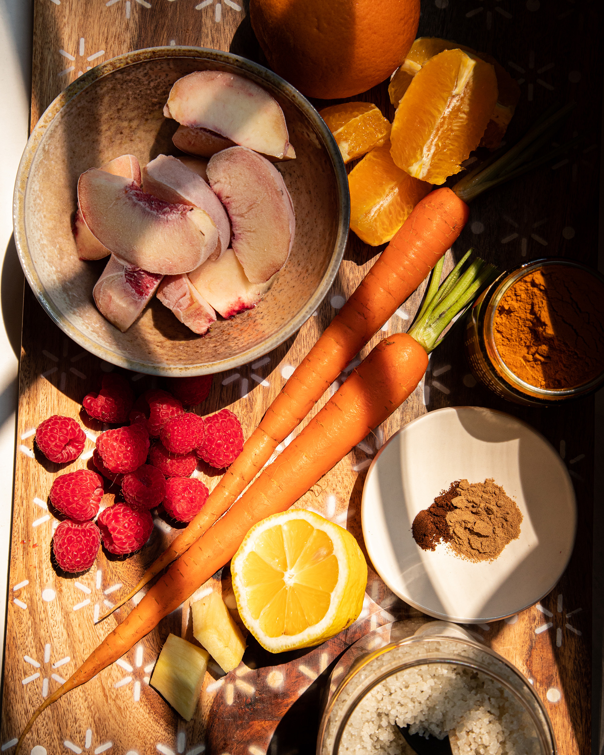 An overhead shot of ingredients for a golden peach sunrise smoothie, shot in harsh light.