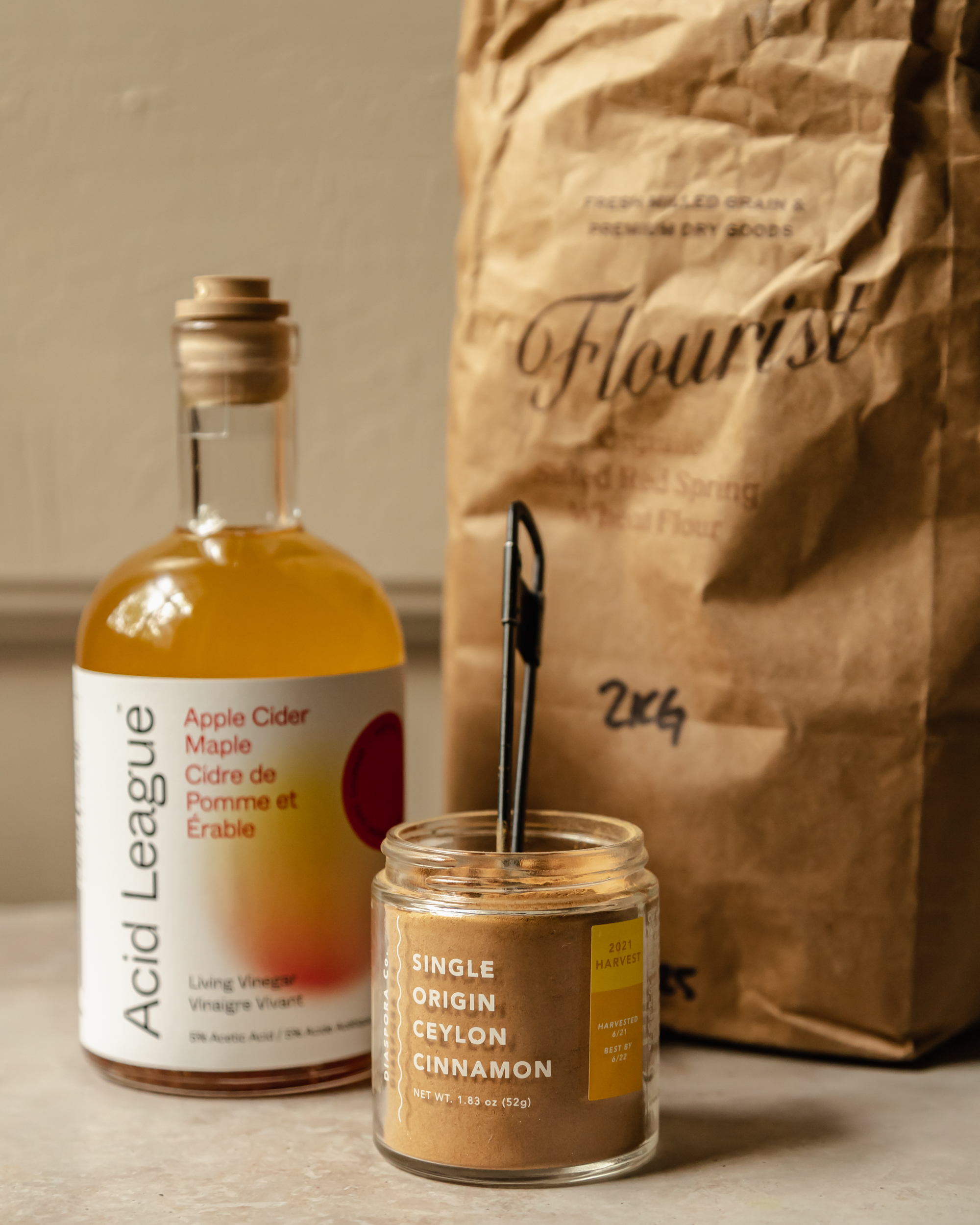 A head-on shot of a jar of ground cinnamon, a bottle of apple cider vinegar and a brown paper bag of flour.