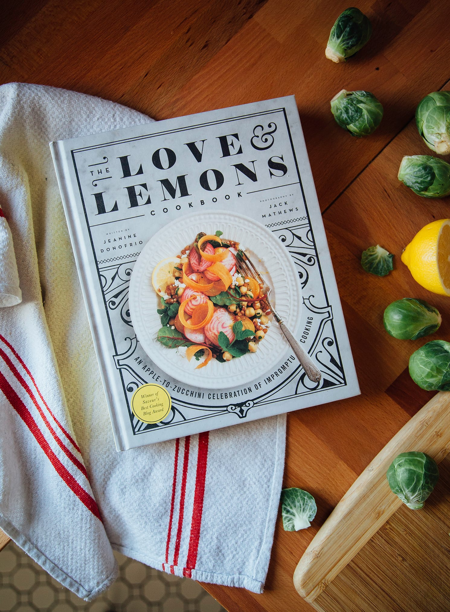 """An overhead shot of """"The Love & Lemons Cookbook"""" on top of a wood butcher block countertop. Brussels sprouts are scattered around nearby."""