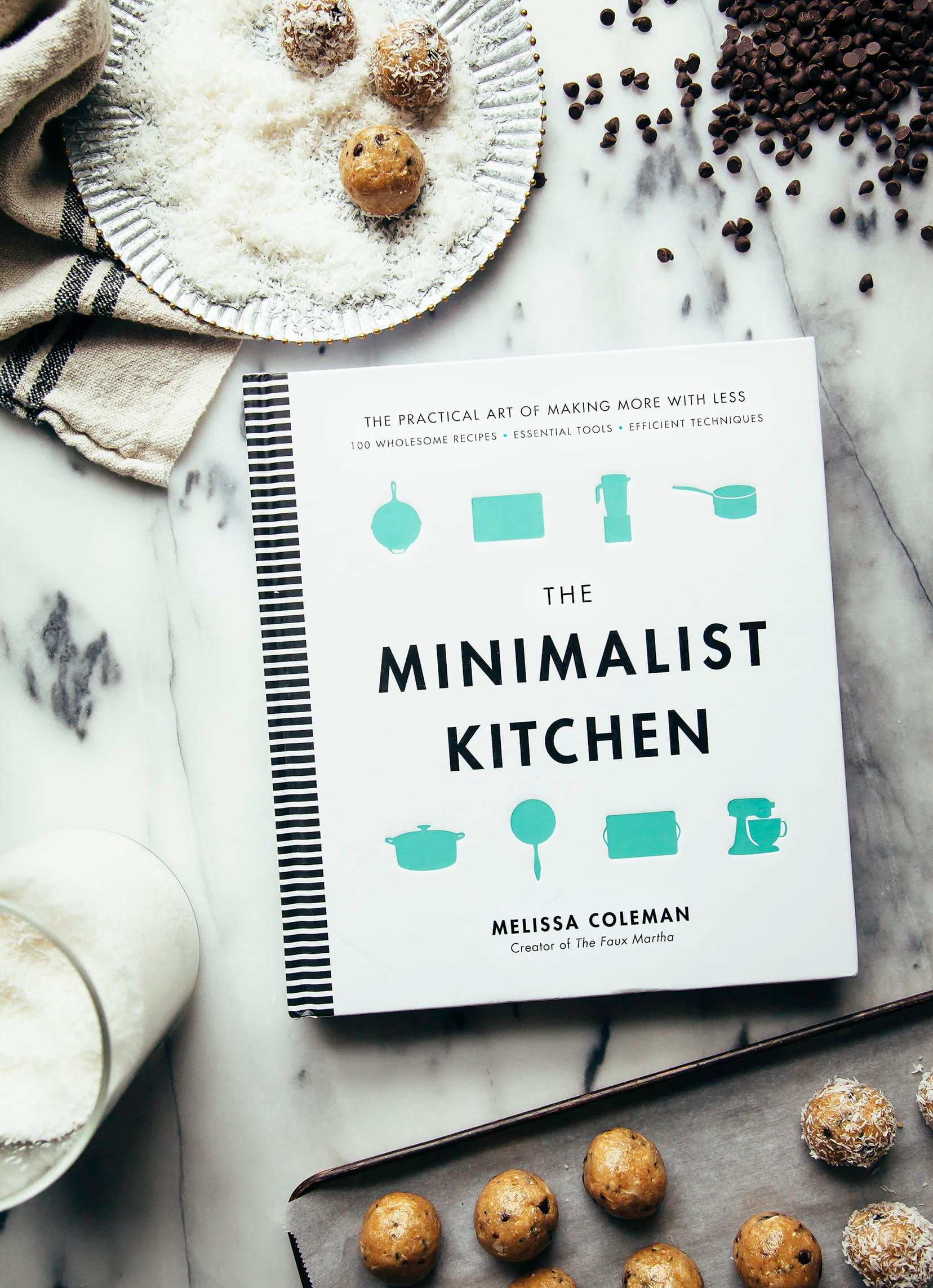 """An overhead shot of """"The Minimalist Kitchen"""" cookbook on a marble background."""