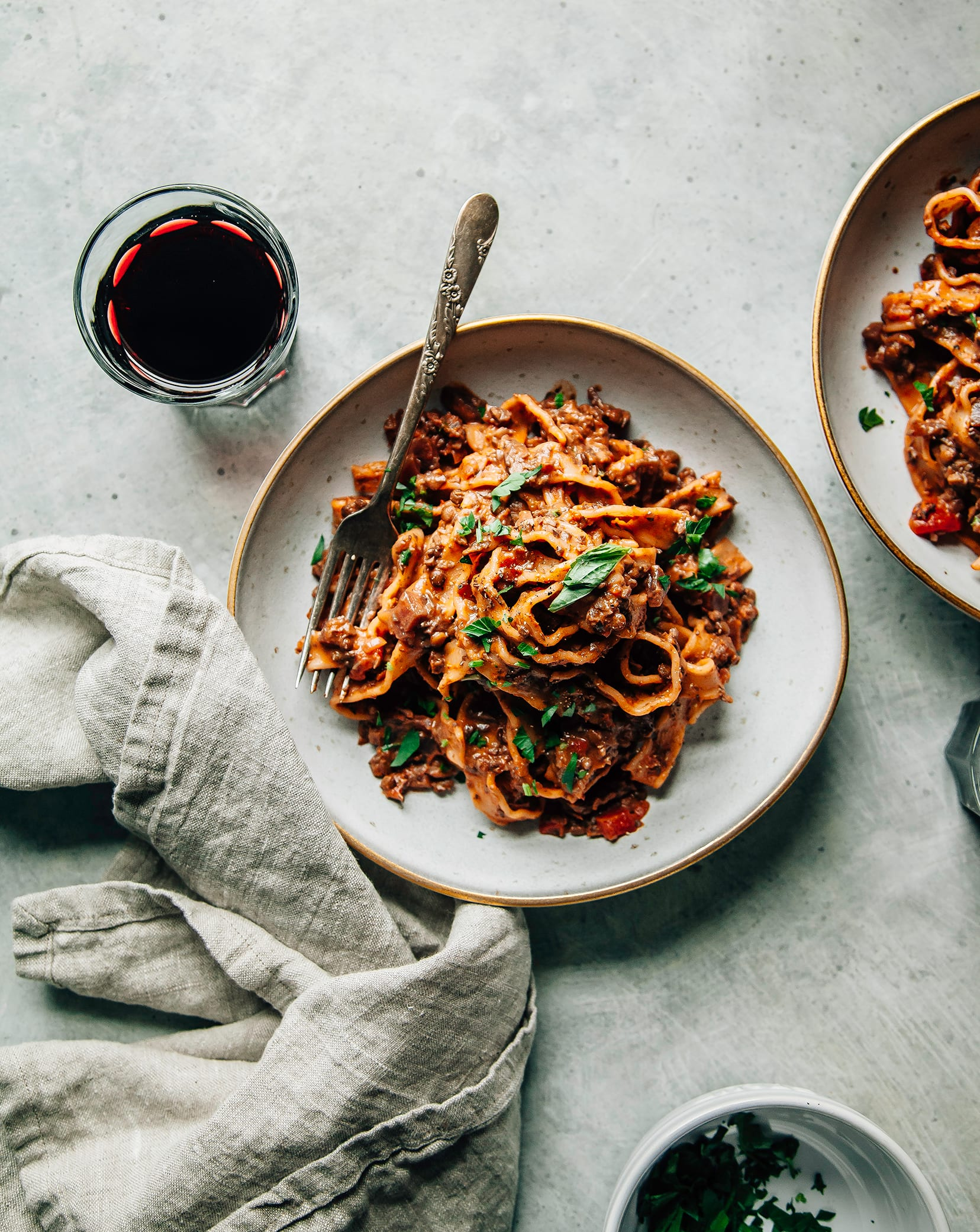 An overhead shot of a deep red mushroom and beet bolognese pasta in two wide serving bowls.