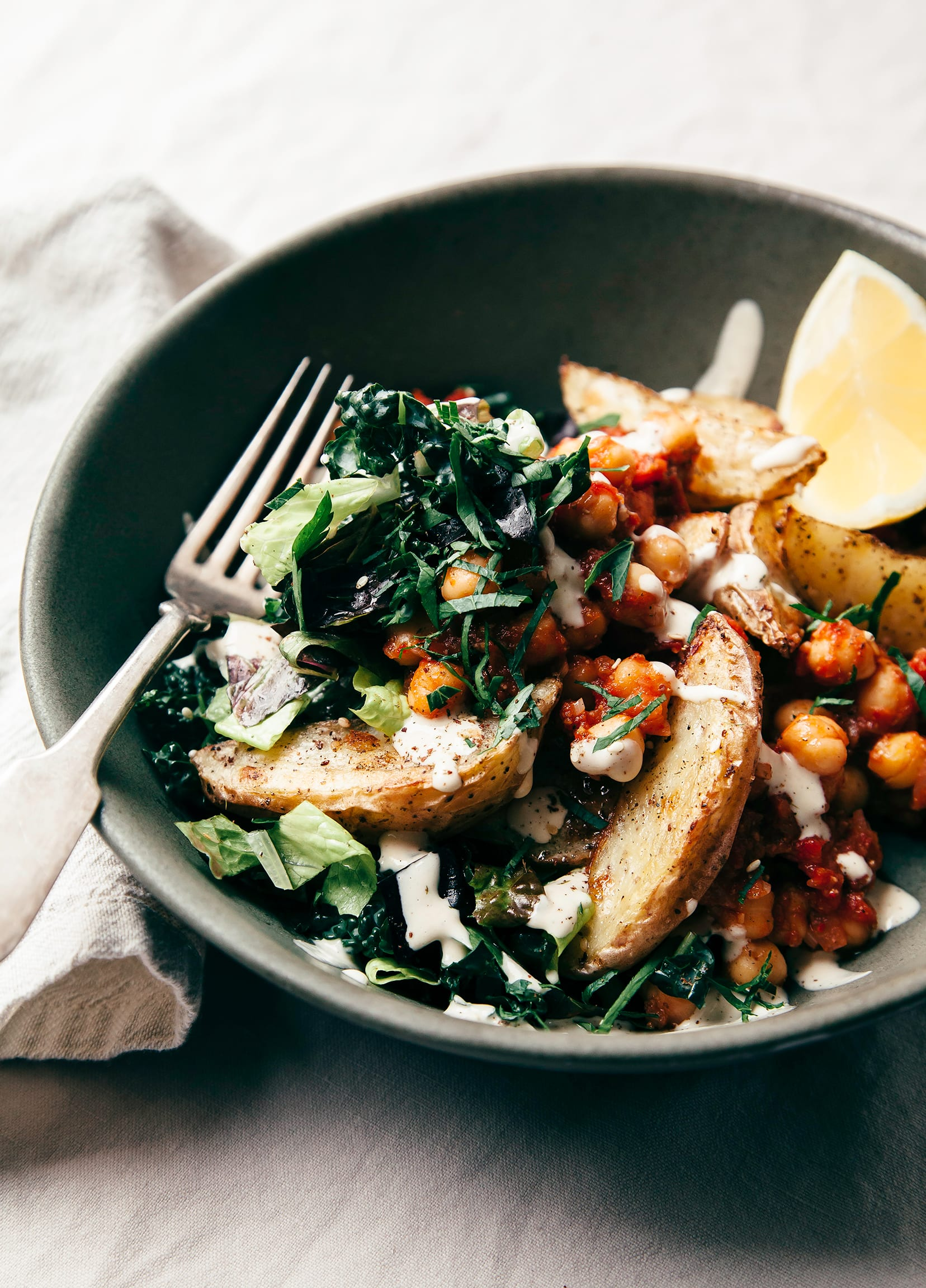 A 3/4 angle shot of a dark green bowl containing: roasted wedges of potatoes, red-sauced chickpeas, a tangle of mixed greens and herbs, and drizzles of a white creamy sauce.
