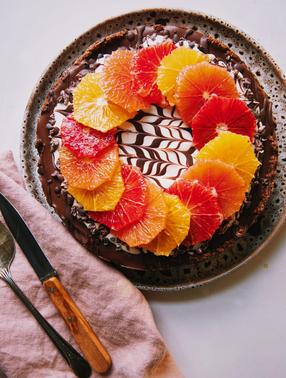 An overhead shot of a vegan chocolate orange cheesecake on a white background. The top of the cheesecake has a wreath or different coloured orange slices on top of a white cashew cream and melted chocolate marble design. To the side is a pink linen napkin, a paring knife and a vintage silver serving utensil.