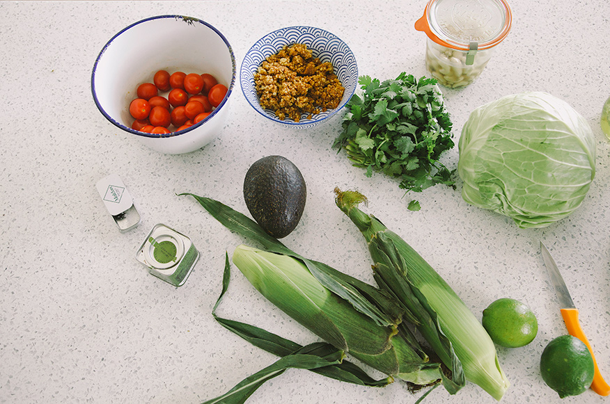 An overhead shot of ingredients for raw and vegan tacos on a white speckled countertop.