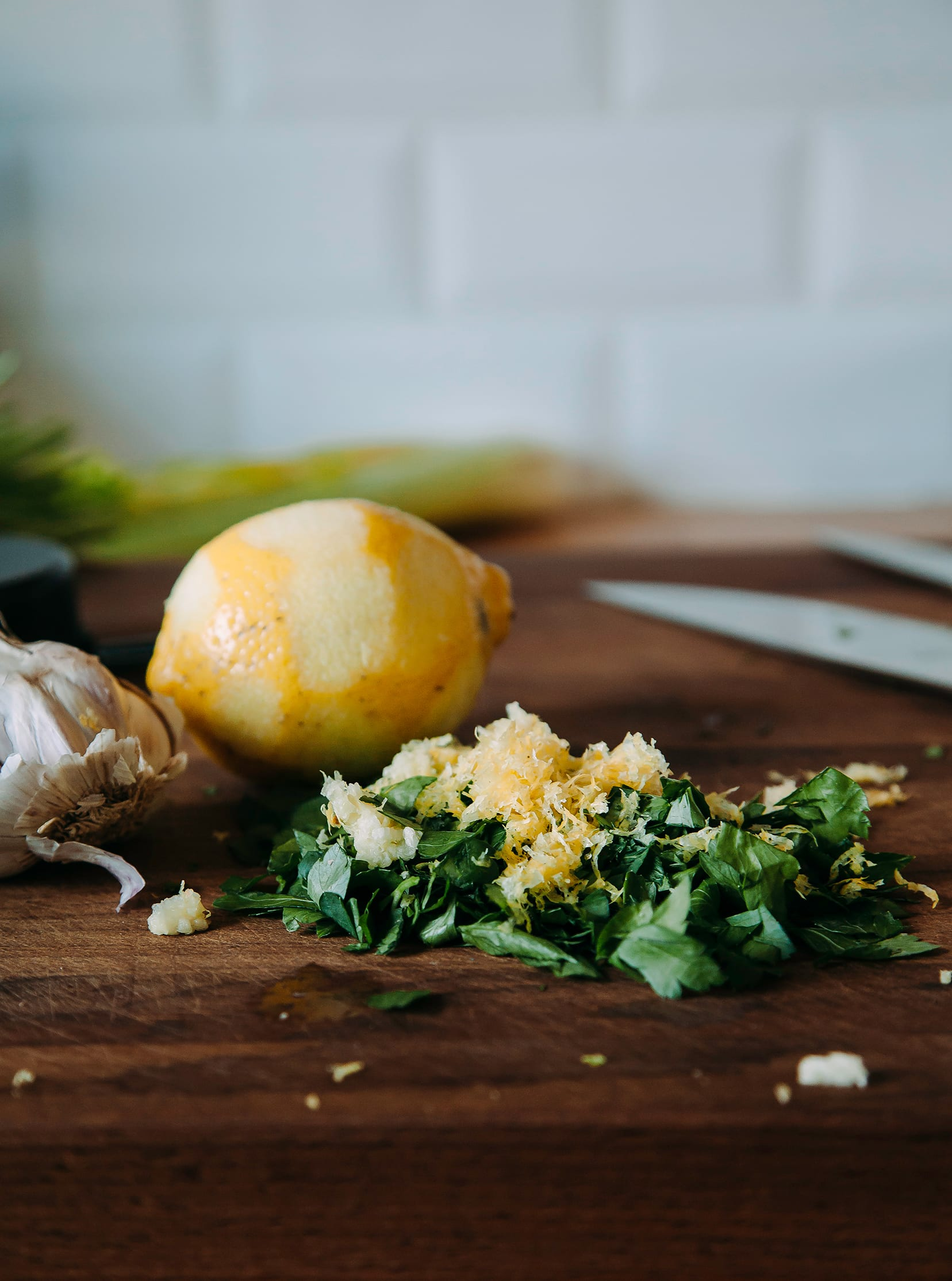 An up close shot of lemon zest mixed with chopped parsley on a cutting board.