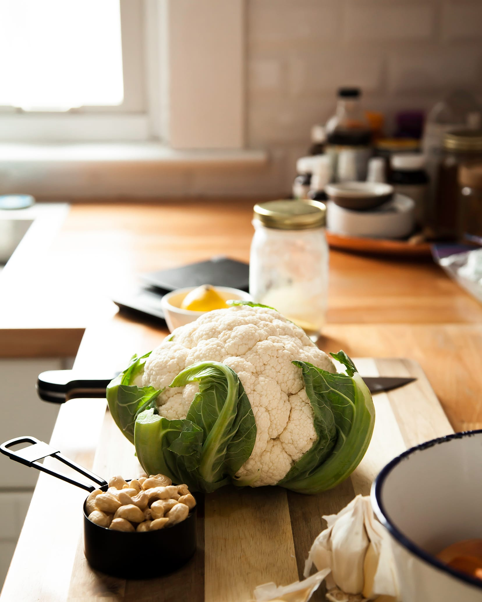 Image shows a head of cauliflower on top of a cutting board in a kitchen scene.