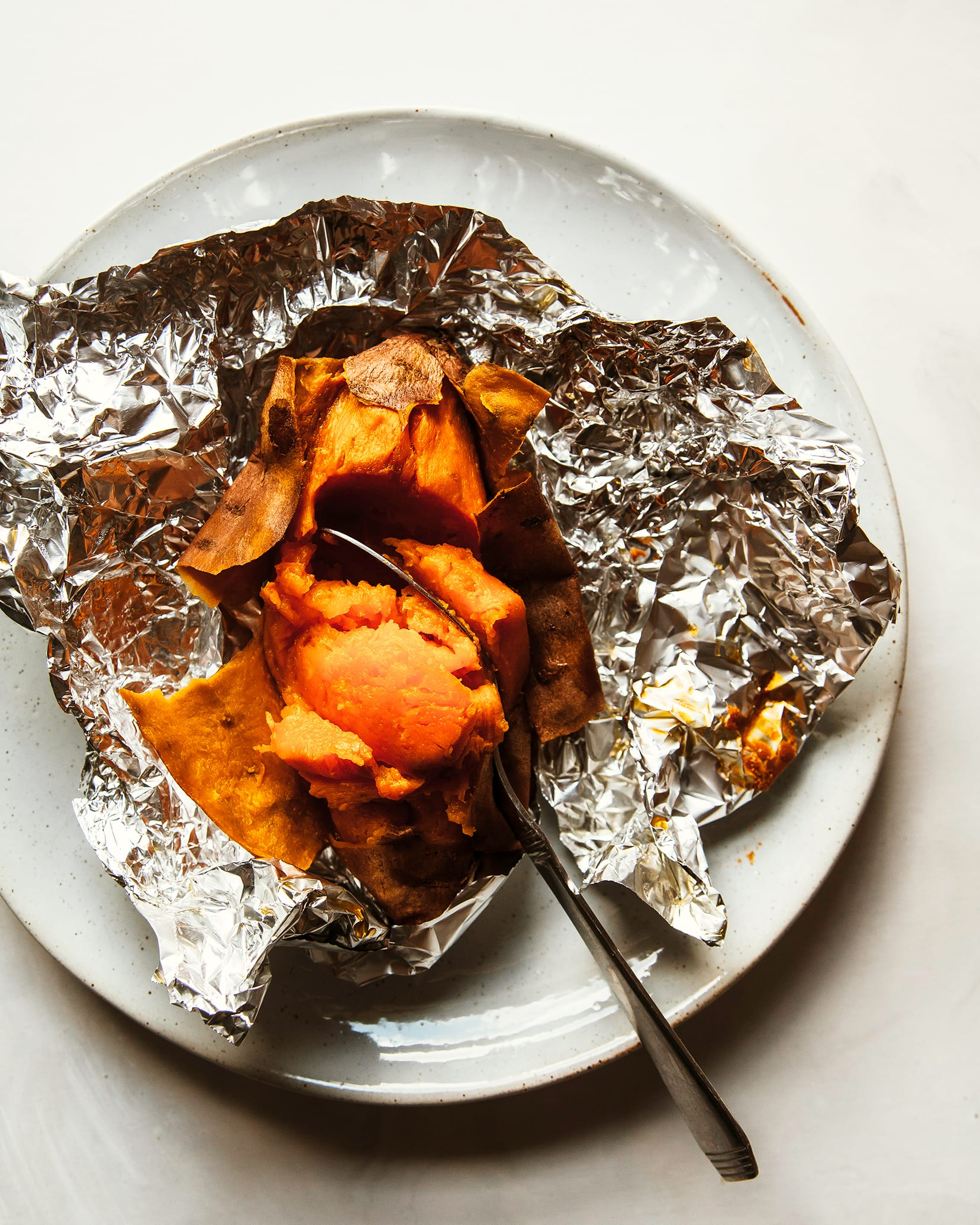 Overhead shot of a baked and opened sweet potato in torn open foil packet on top of a white plate.