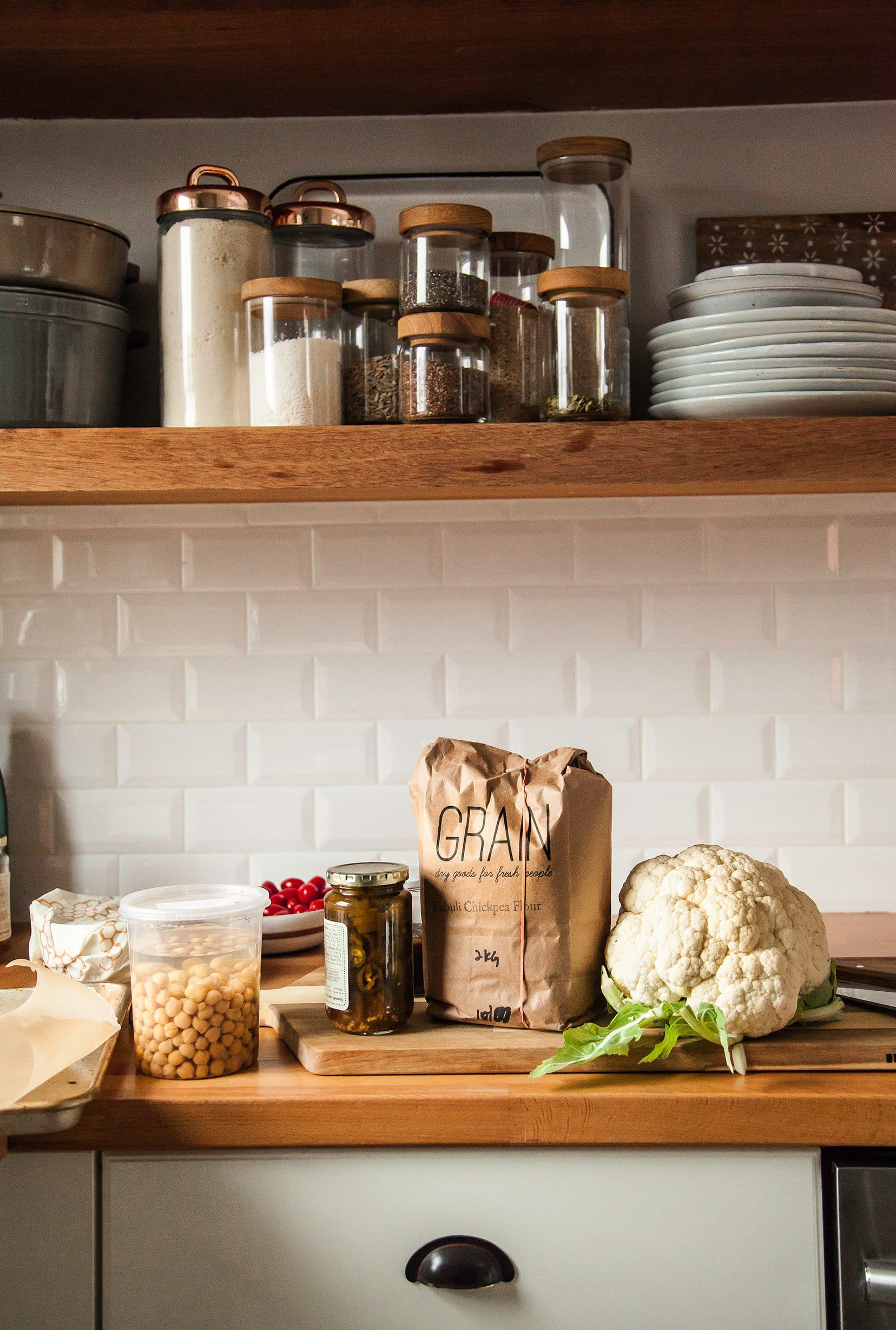 Image shows ingredients for a salad on a butcher block countertop in a white tiled kitchen.