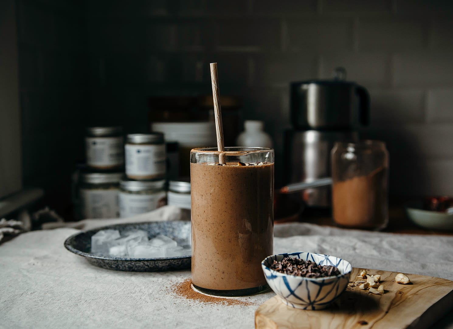 A head-on shot of a double chocolate espresso smoothie that is garnished with chopped hazelnuts and cacao nibs. The smoothie is on top of a beige tablecloth with a small bowl of cacao nibs to the side.