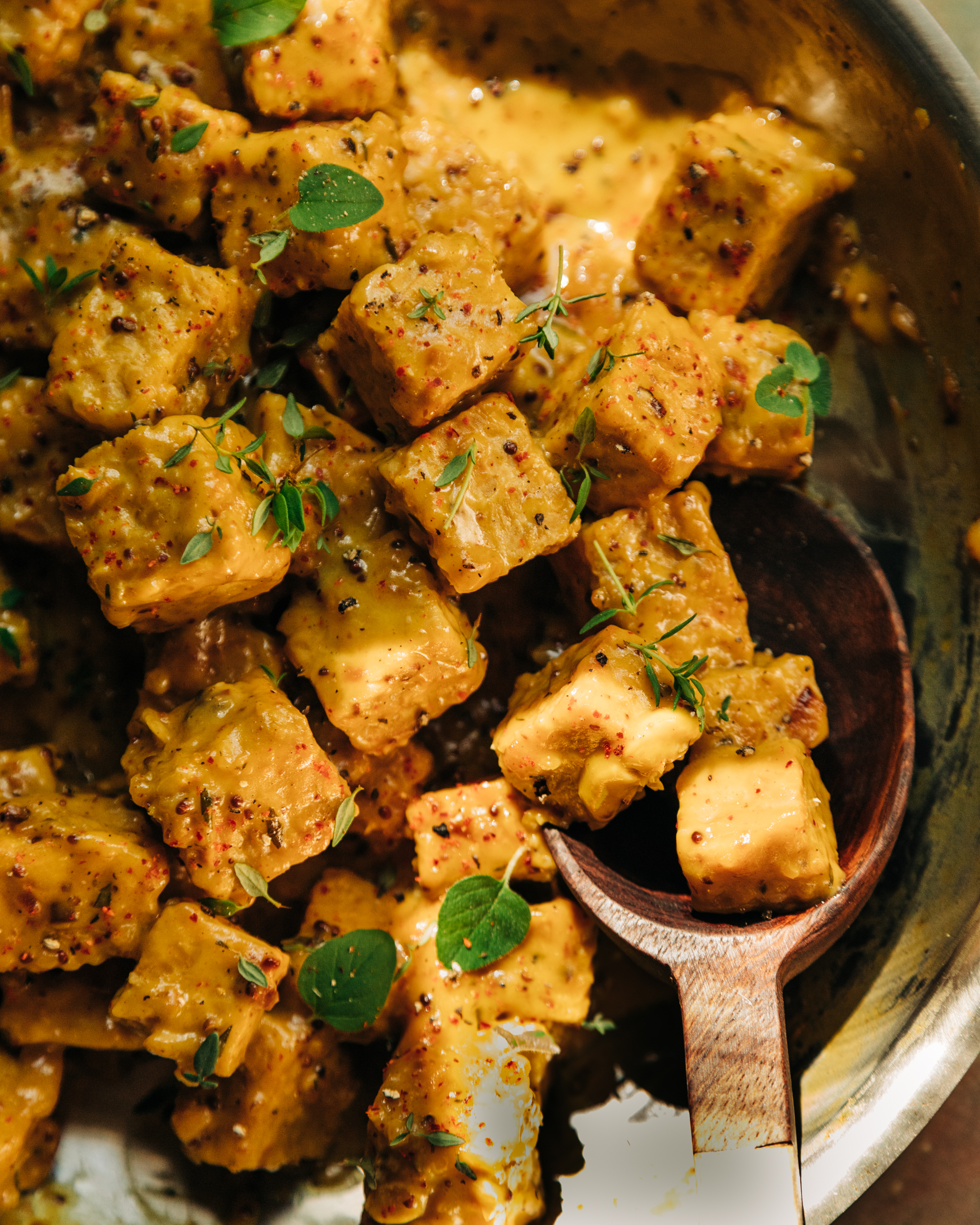 An overhead shot of saucy chunks of maple mustard tempeh tempeh in a skillet. The sauce is golden yellow and the tempeh is garnished with fresh thyme and oregano leaves.