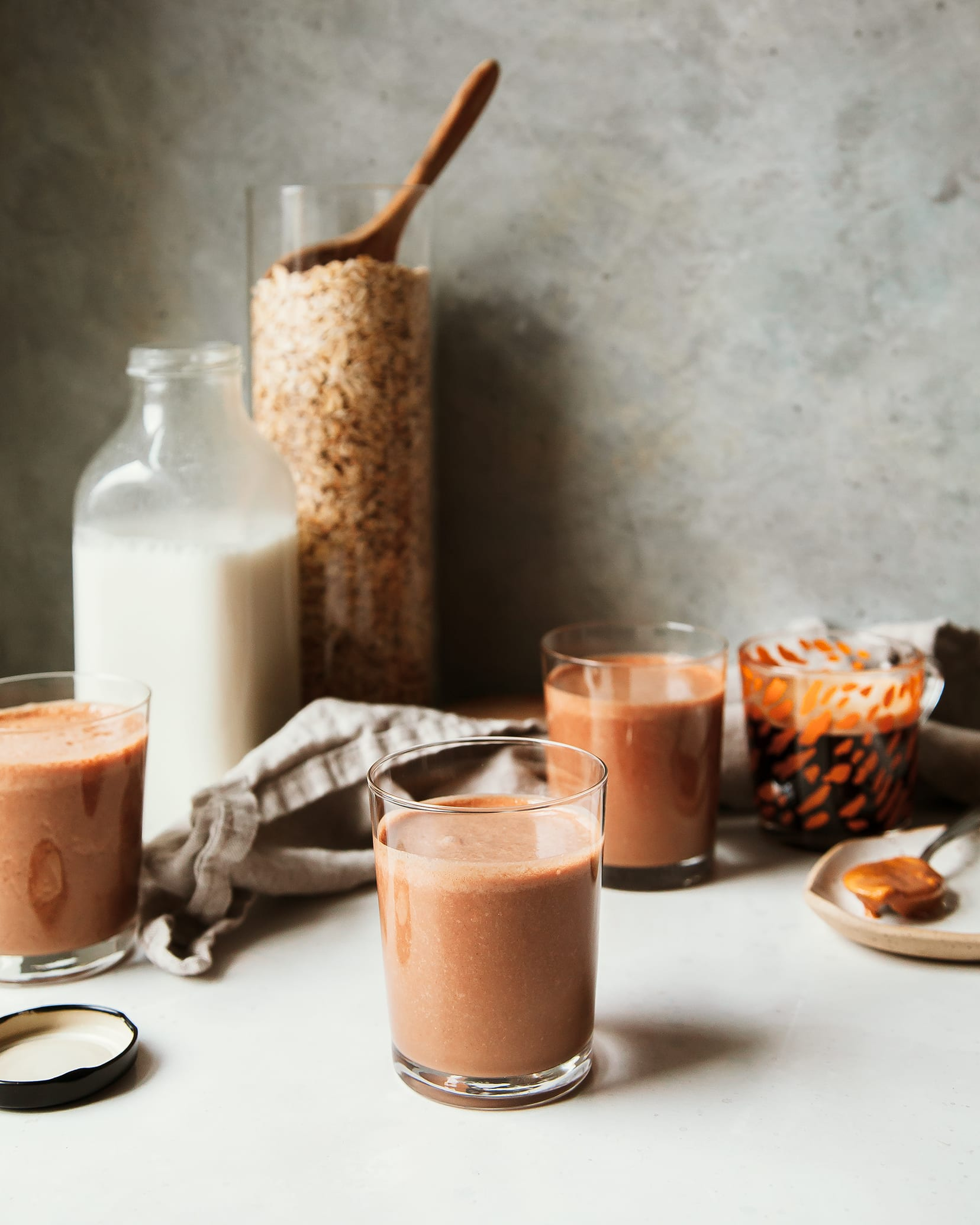 A head on shot of a thick peanut butter mocha smoothie that is rich, chocolate brown in colour. In the background, there is a clear bottle of homemade non-dairy milk and a big clear jar of oats.