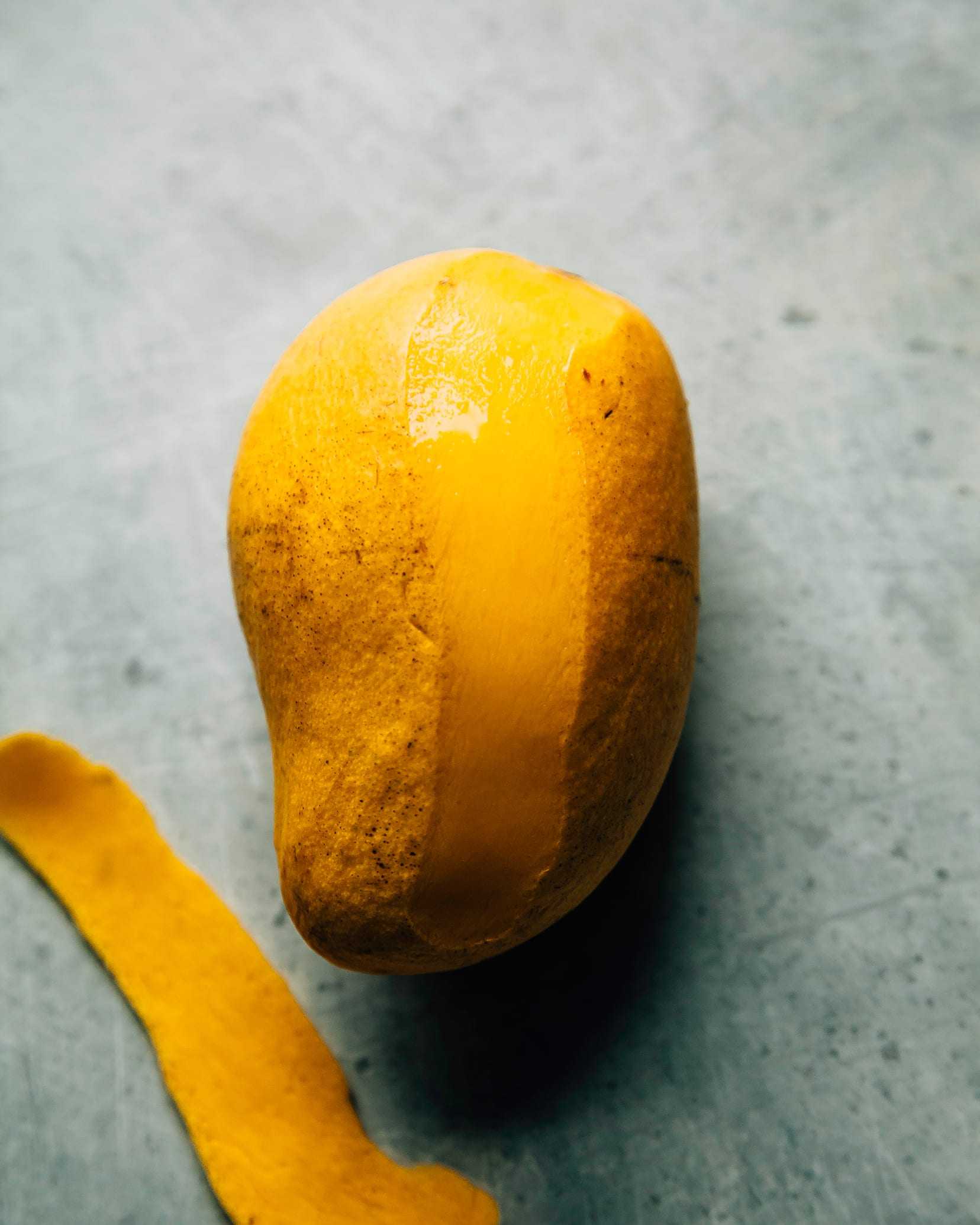 A ripe Ataulfo mango on a pale blue background with a strip of peel removed.