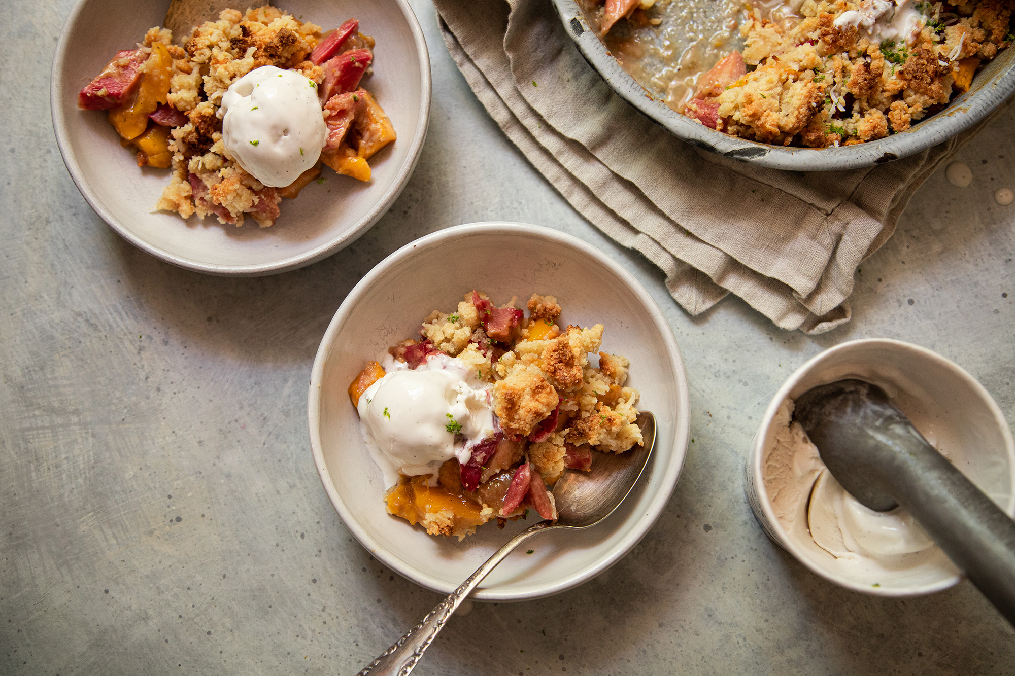 An overhead shot of a fruit crumble dessert in white serving bowls. Each serving is topped with a melt-y scoop of ice cream.