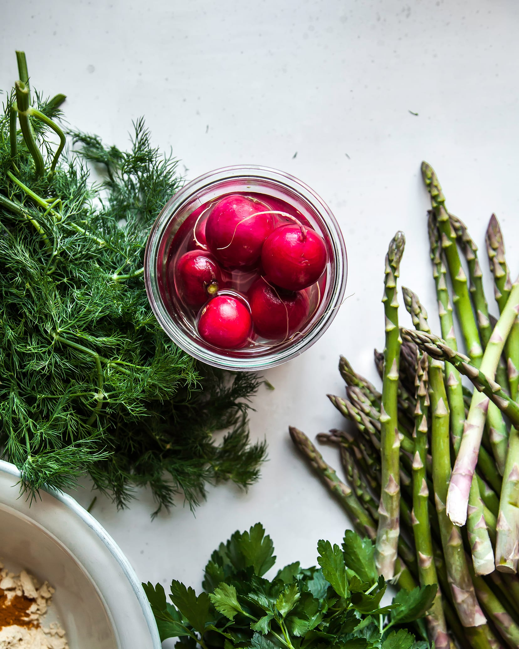 An overhead shot of asparagus, radishes and fresh dill on a white background.