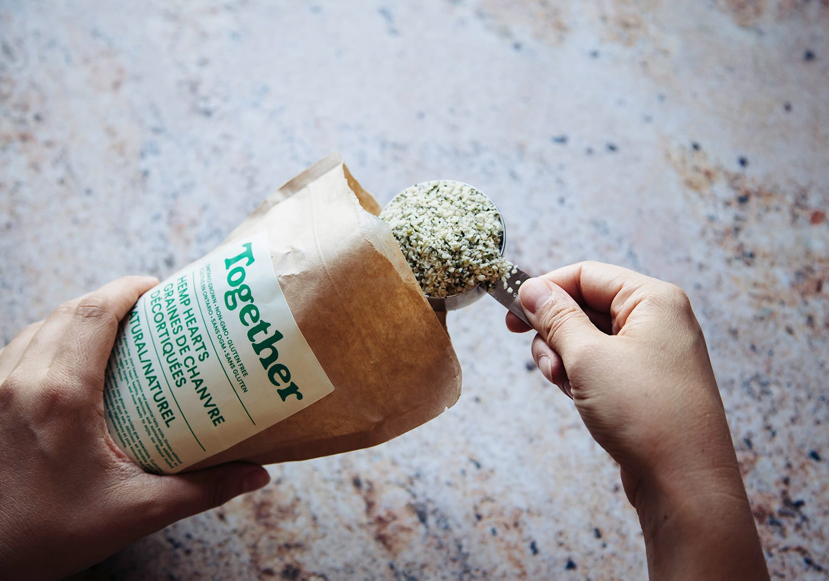An overhead shot of a hand scooping some hemp seeds from a brown paper bag.