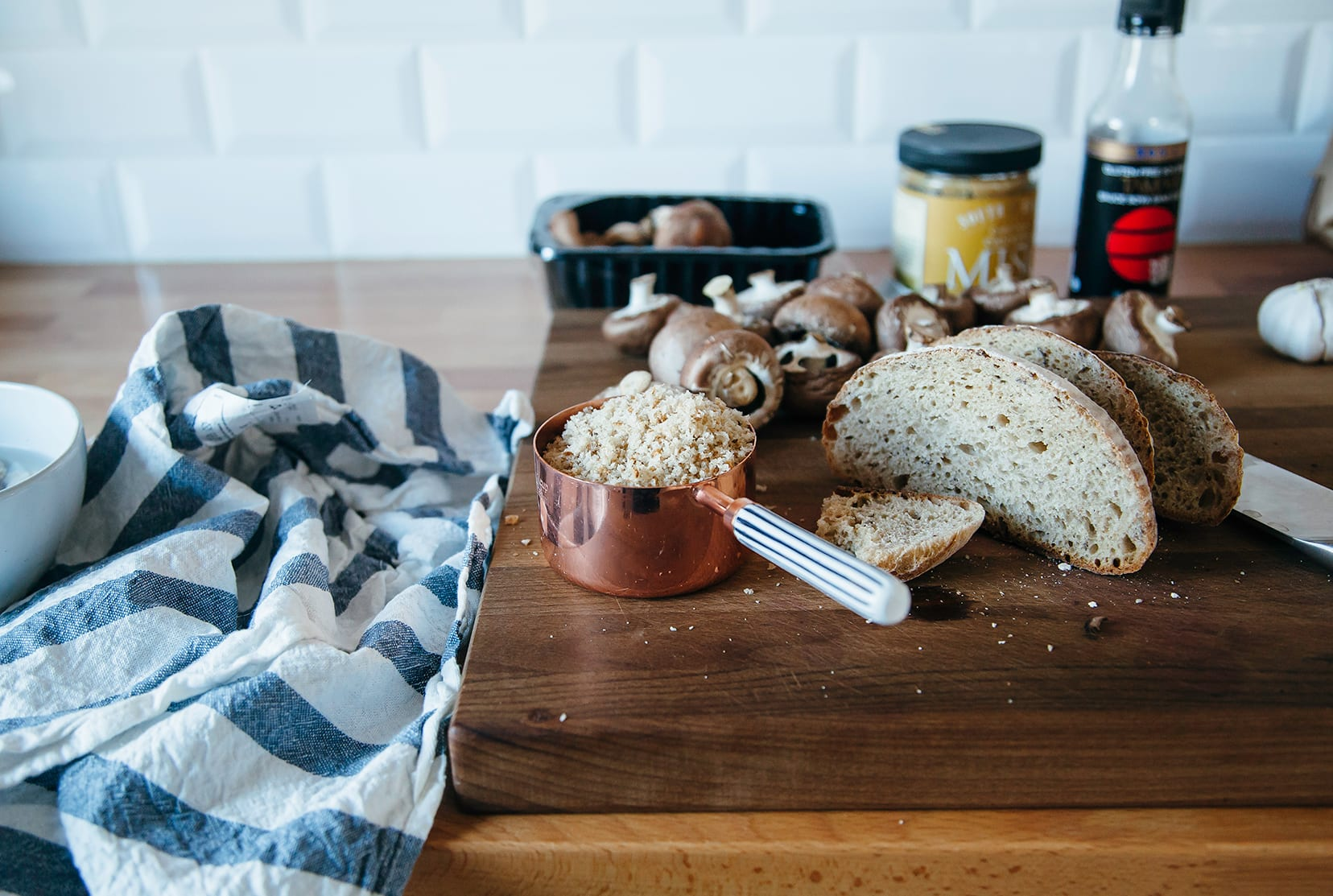Image shows a cutting board with bread, mushrooms, and condiments on top.