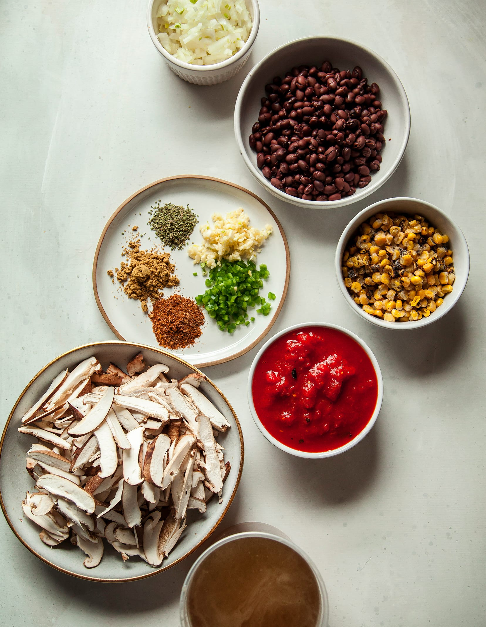An overhead shot of ingredients, including: spices, garlic, jalapeño, canned crushed tomatoes, sliced shiitake mushrooms, black beans, corn, and diced onion. All on a white background.