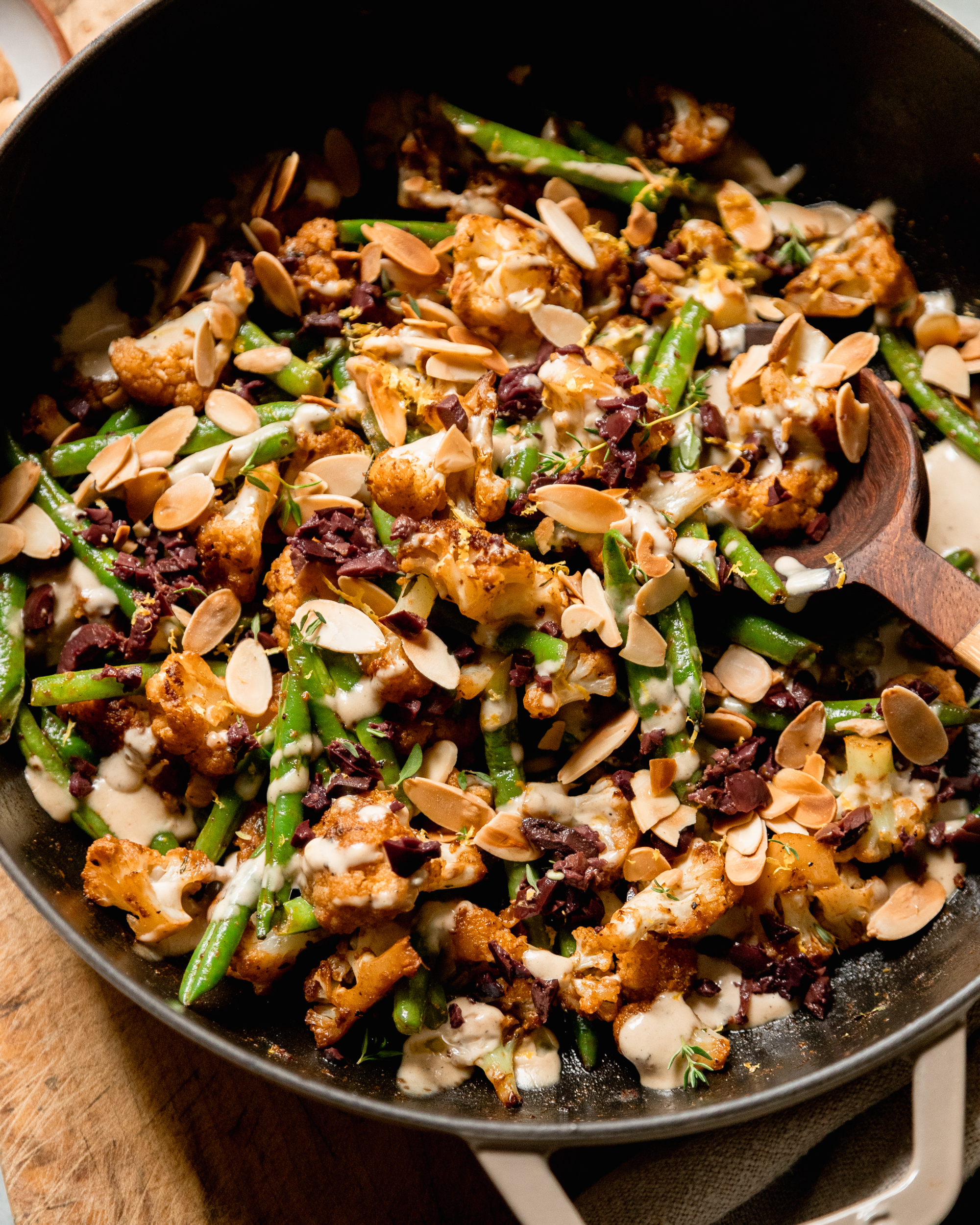 An up close, overhead shot of a sautéed cauliflower and green bean dish that is topped with a creamy sauce, chopped olives, and sliced almonds.