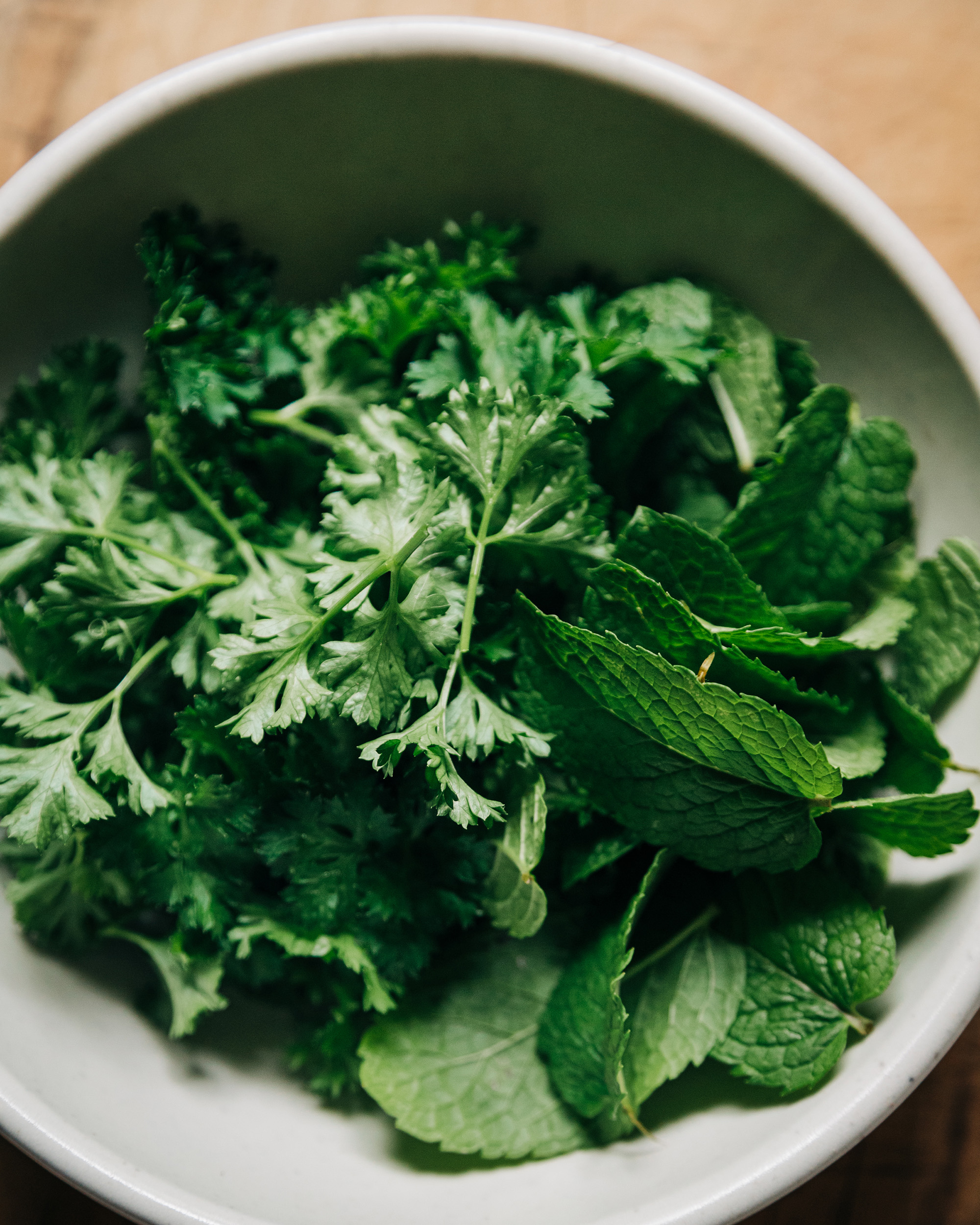 An up close, overhead shot of parsley and mint leaves in a white bowl.