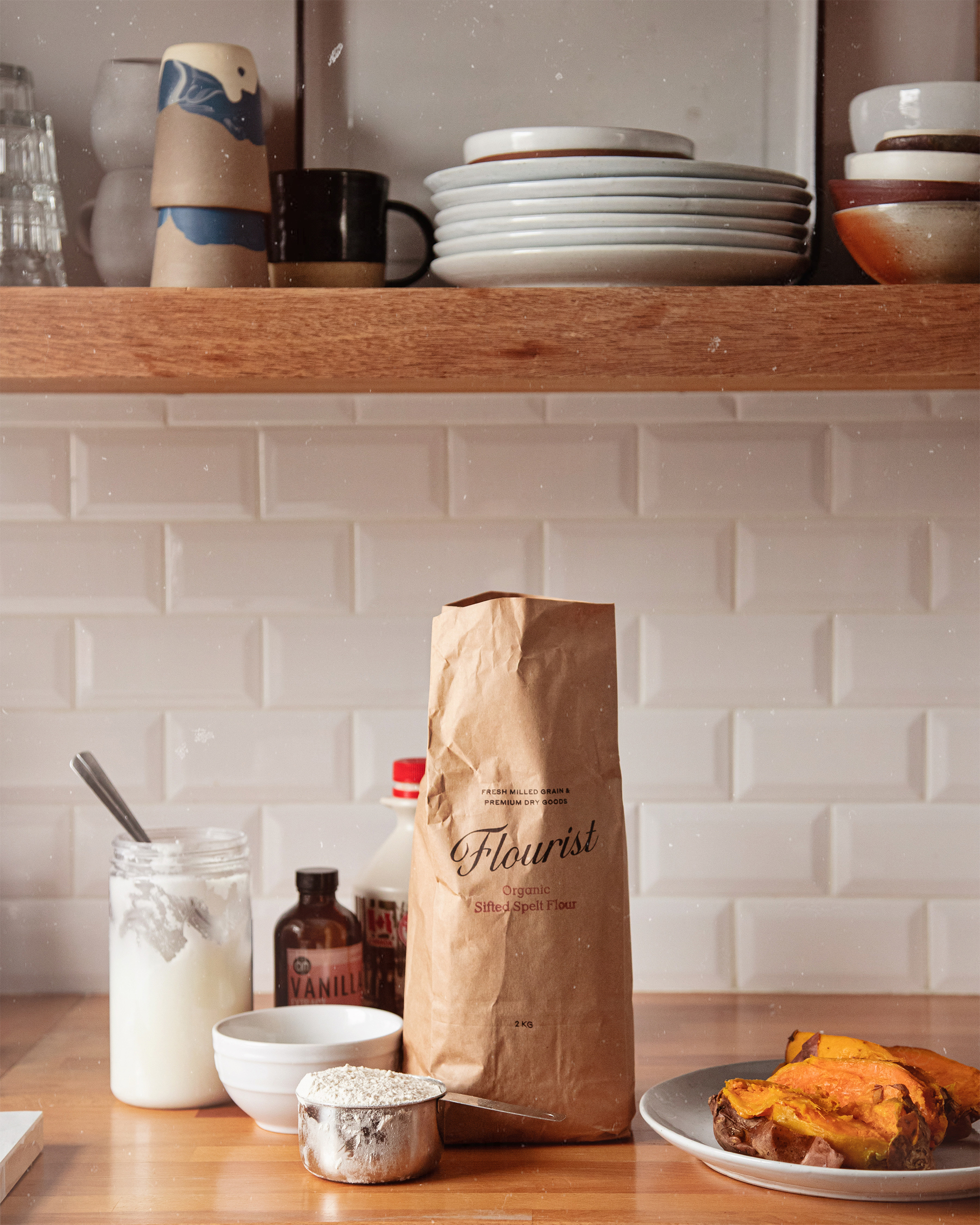 A head on shot of muffin ingredients on a wood butcher block counter with open shelving and white subway tile in the background.