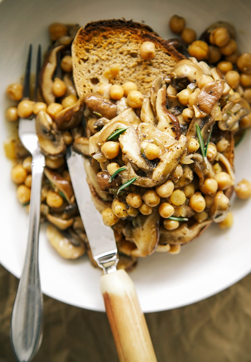 Image shows cooked mushrooms and chickpeas in a light gravy on top of a piece of whole grain toast. The image is shot from overhead.