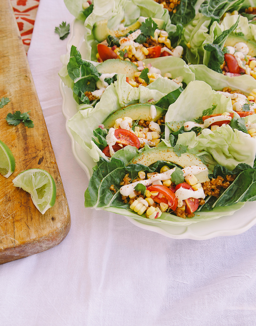 A 3/4 angle shot of a platter of raw and vegan tacos, all encased in cabbage and chard leaves.