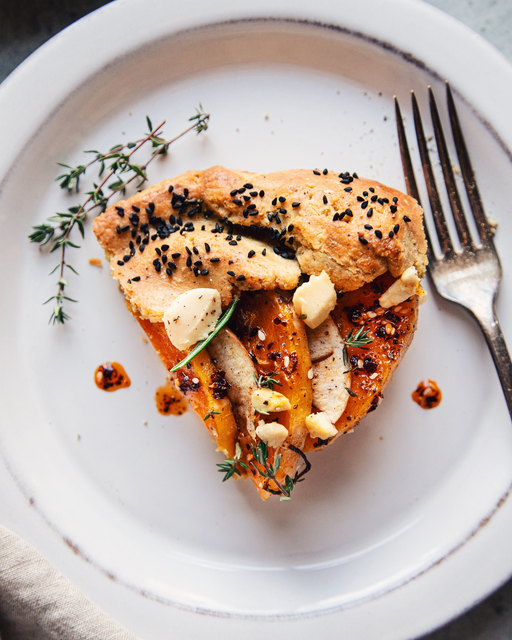 An overhead, up close shot of a slice of vegan butternut galette on a weathered white plate.