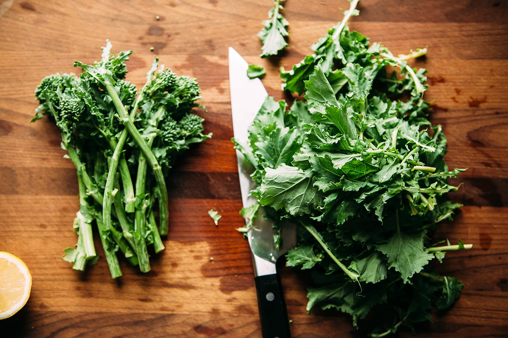 Overhead shot of trimmed broccoli rabe stalks and leaves on a wood cutting board.