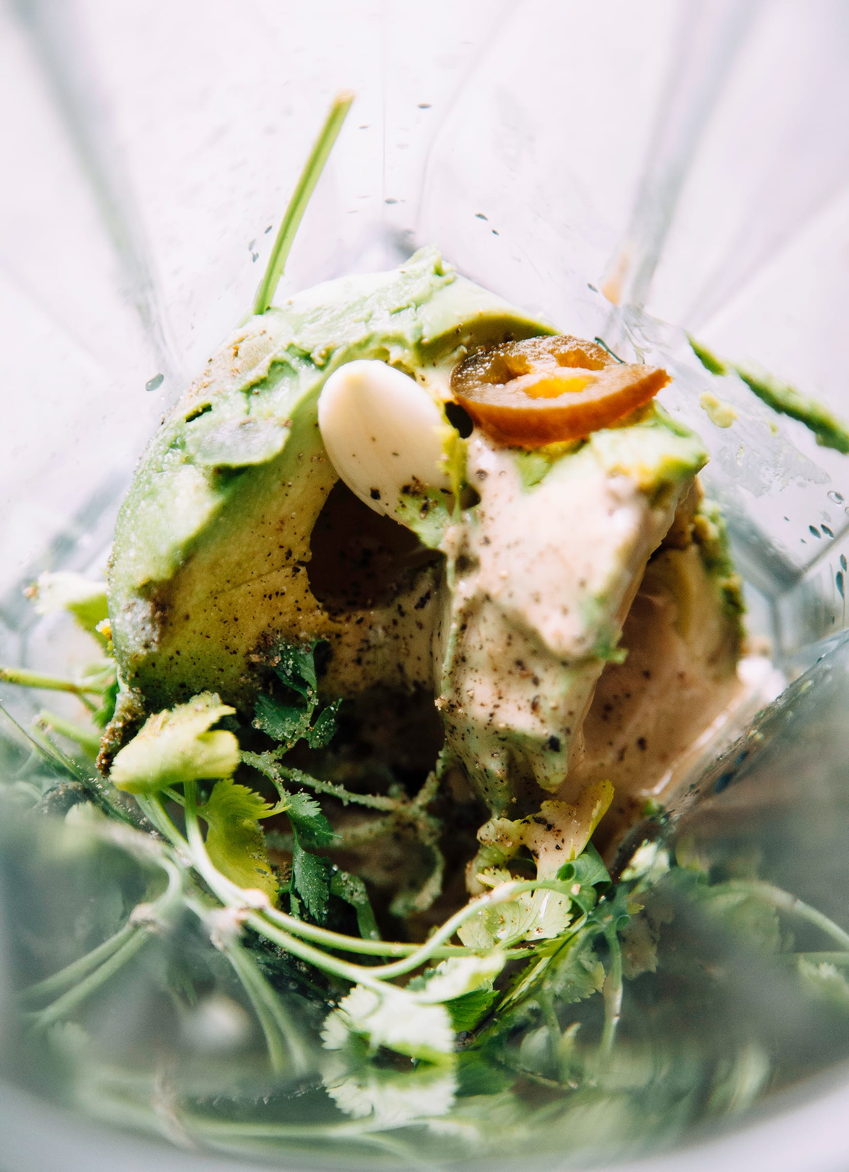 Overhead shot of the contents of a blender pitcher: avocado, cilantro, tahini, jalapeno, garlic, salt, and pepper.