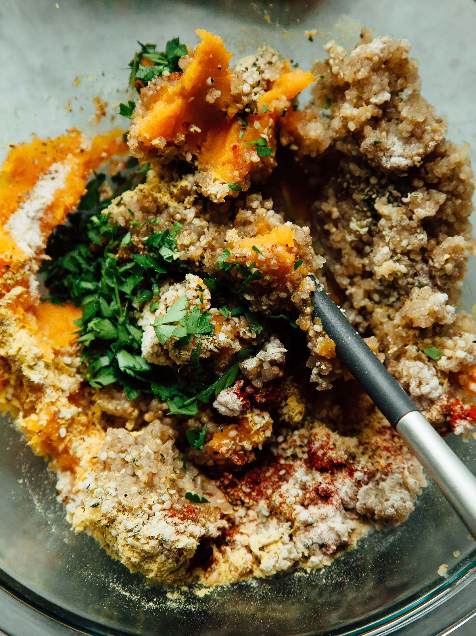 An overhead shot of a quinoa, mashed sweet potato, and herb mixture in a bowl with a spatula.