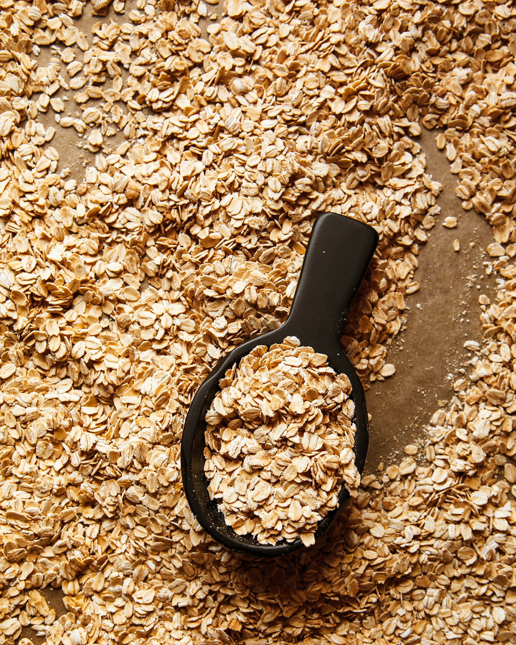 Overhead shot of toasted oats with a black scoop.