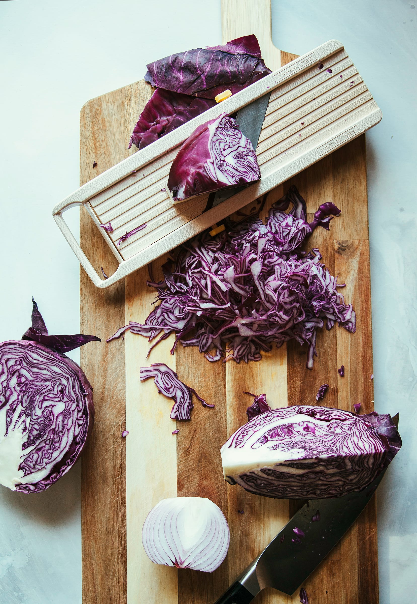 Overhead image of red cabbage being shredded with a mandolin over a wood cutting board.